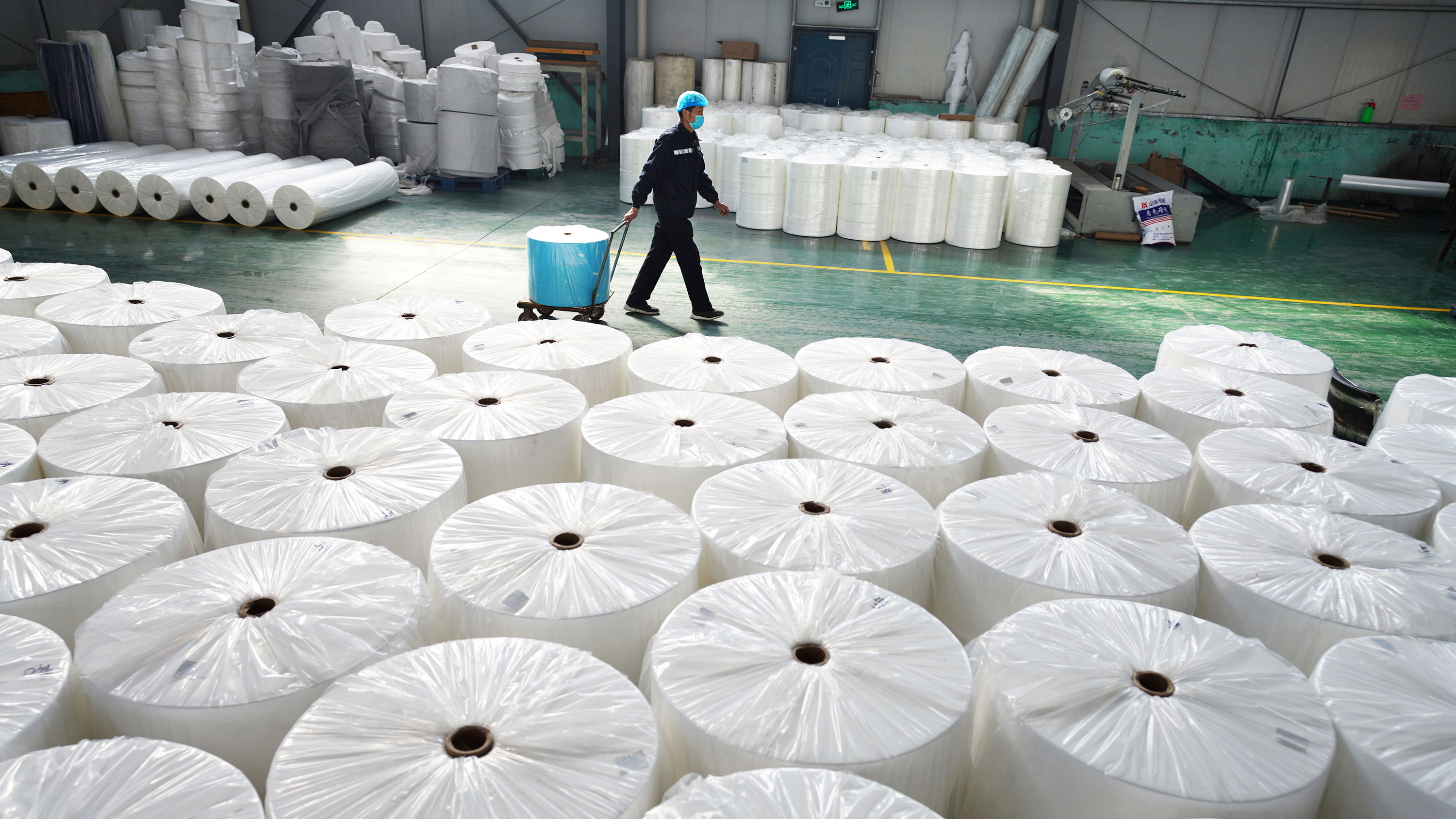 Picture shows a large factory space with a massive stack of large fabric spools in the foreground and a single worker walking by in the background.