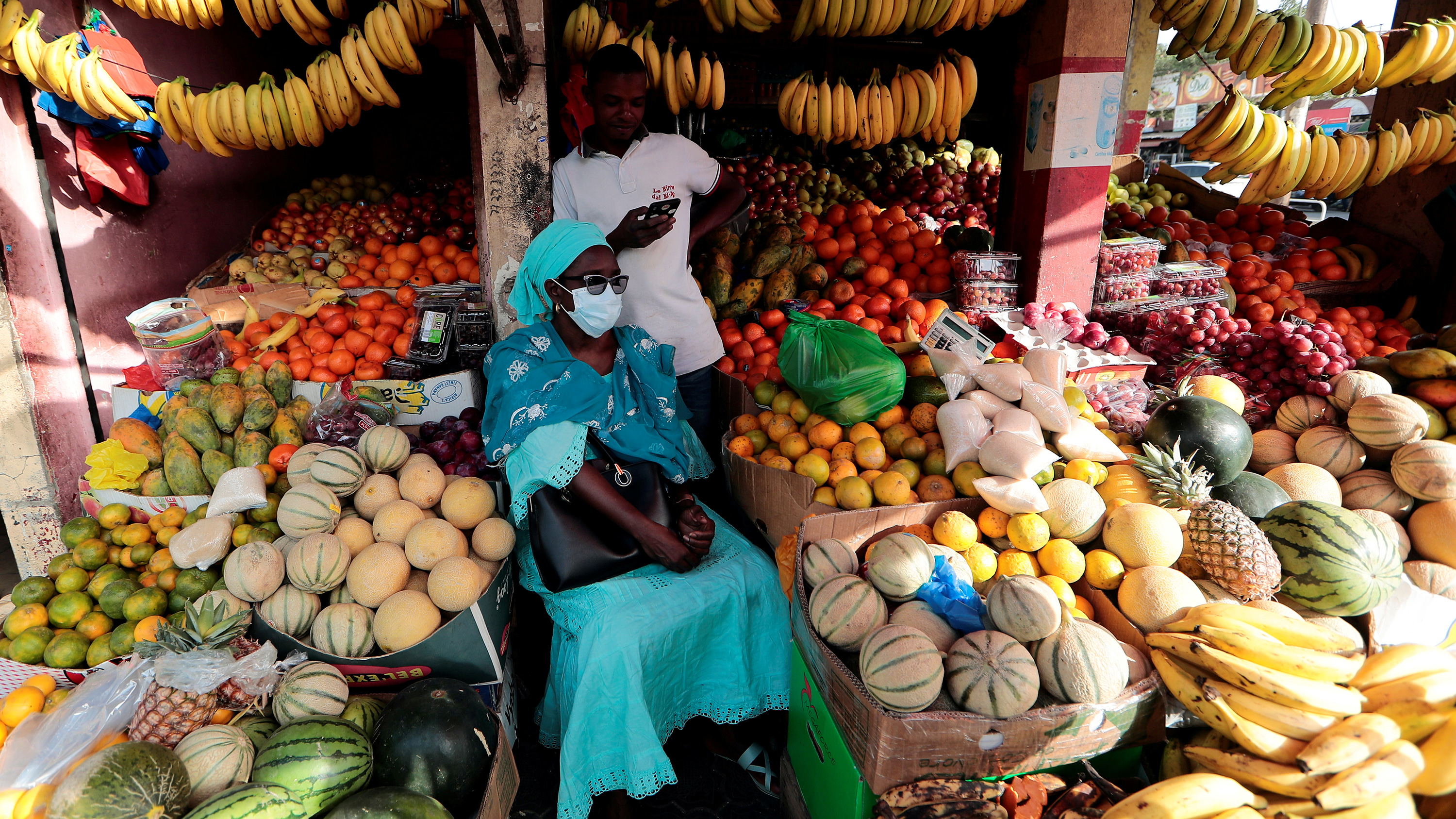 The photo shows a woman wearing a mask sitting amid an abundance of fruit in a tiny stand.