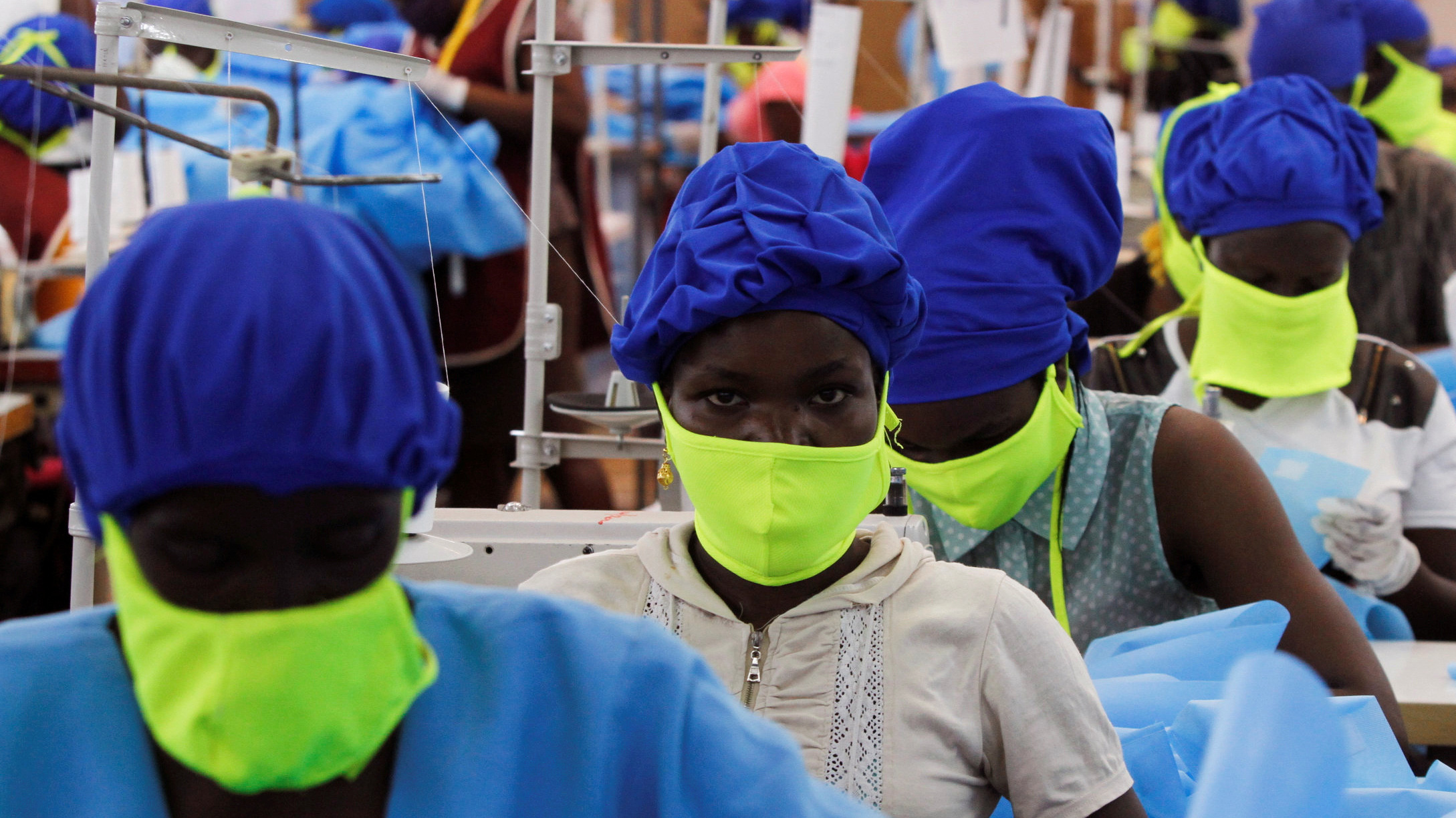 The photo shows a row of workers wearing protective blue suits and bright green facemasks working in a factory.