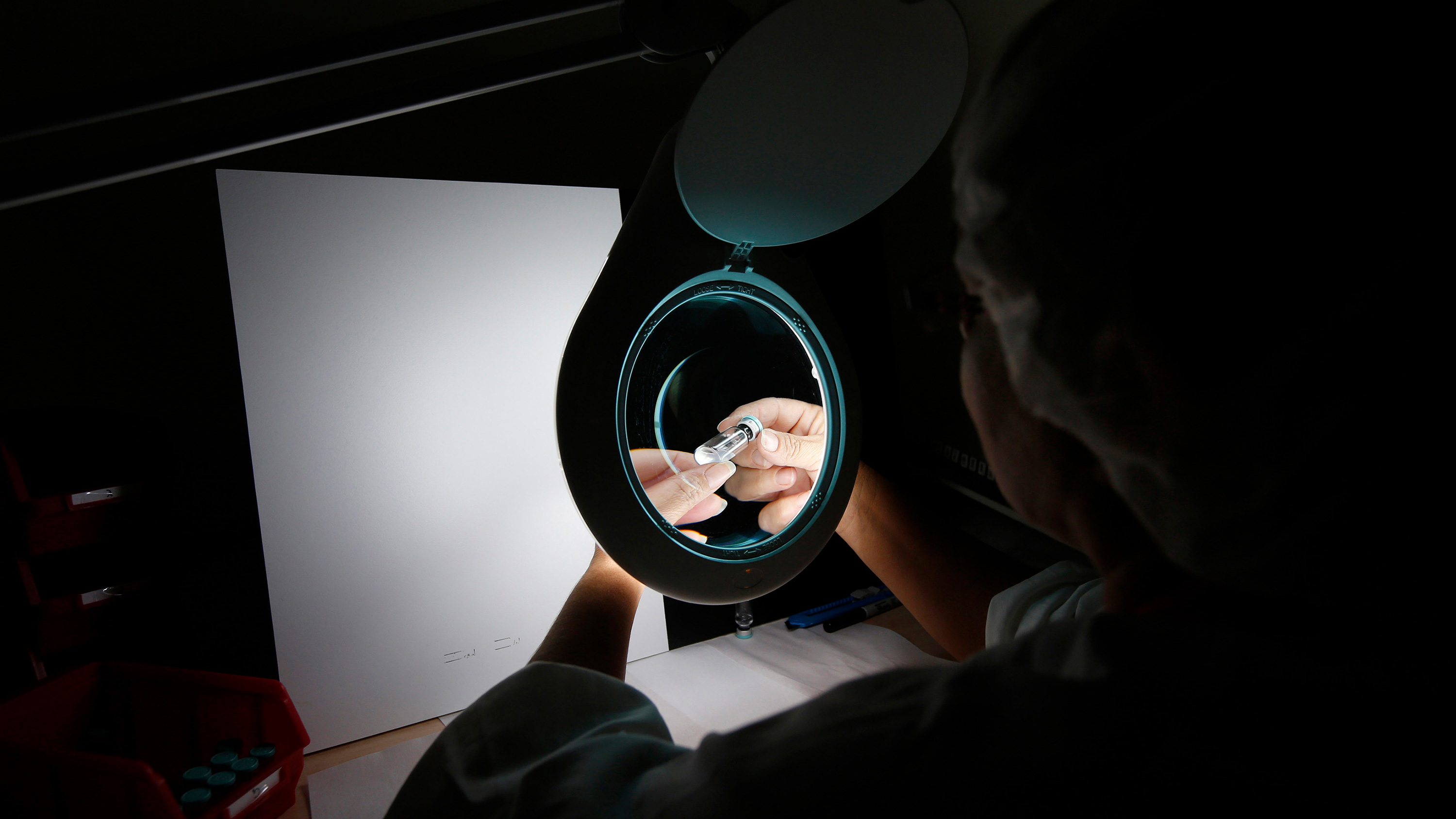 Picture taken shows a laboratory worker at a darkened bench looking at a tiny vial under a lighted magnifying lens.