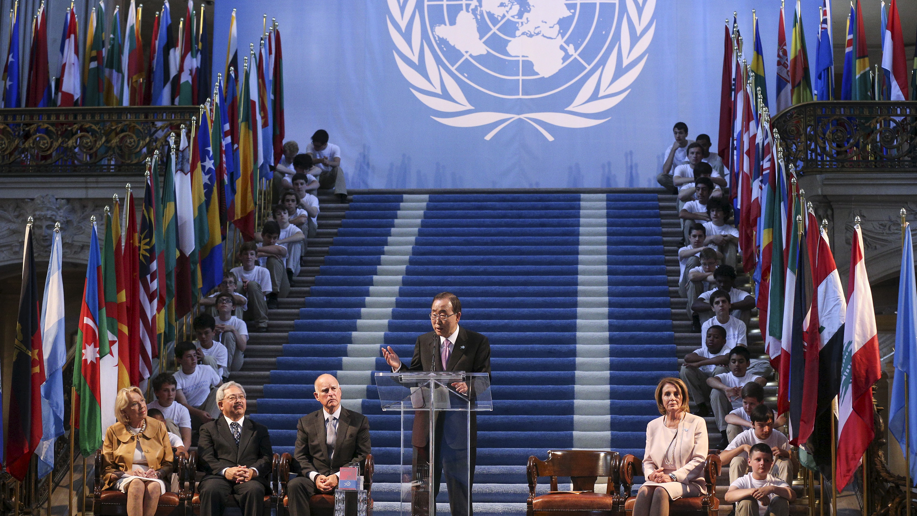 The photo shows the former UN Secretary-General at a podium on an elaborately designed stage with steps leading up and children dressed in white shirts and tan slacks on either sides of the stairs.