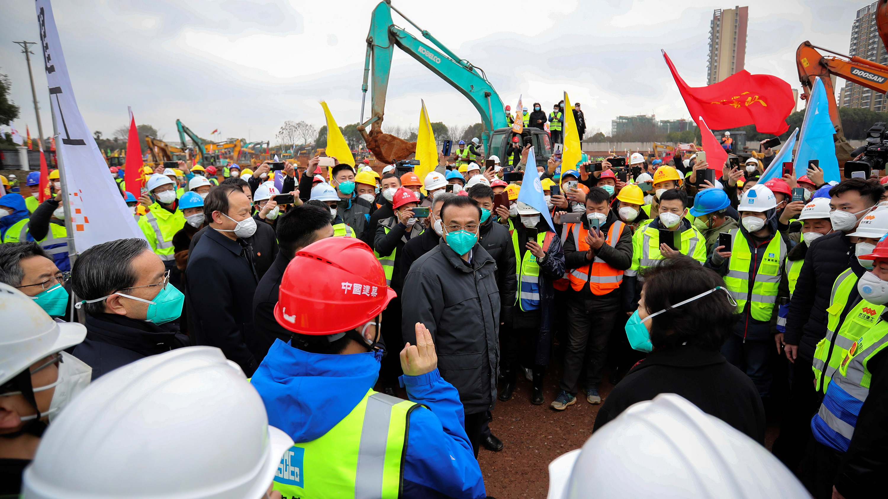 Photo shows the leader surrounded by construction workers and other people at the construction site with huge cranes looming in the background.