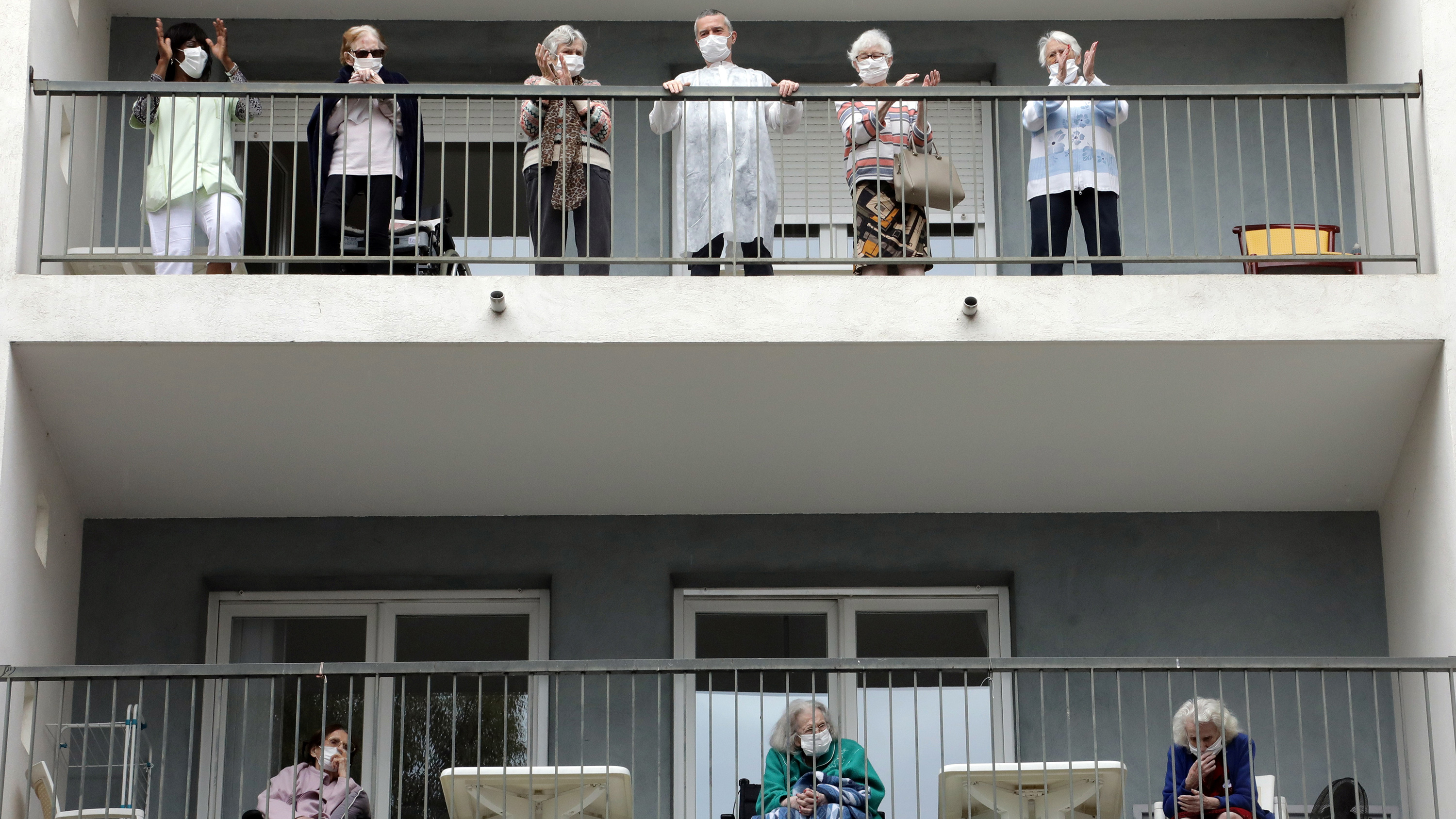 The photo shows two rows of balconies lined with elderly people watching the performance.