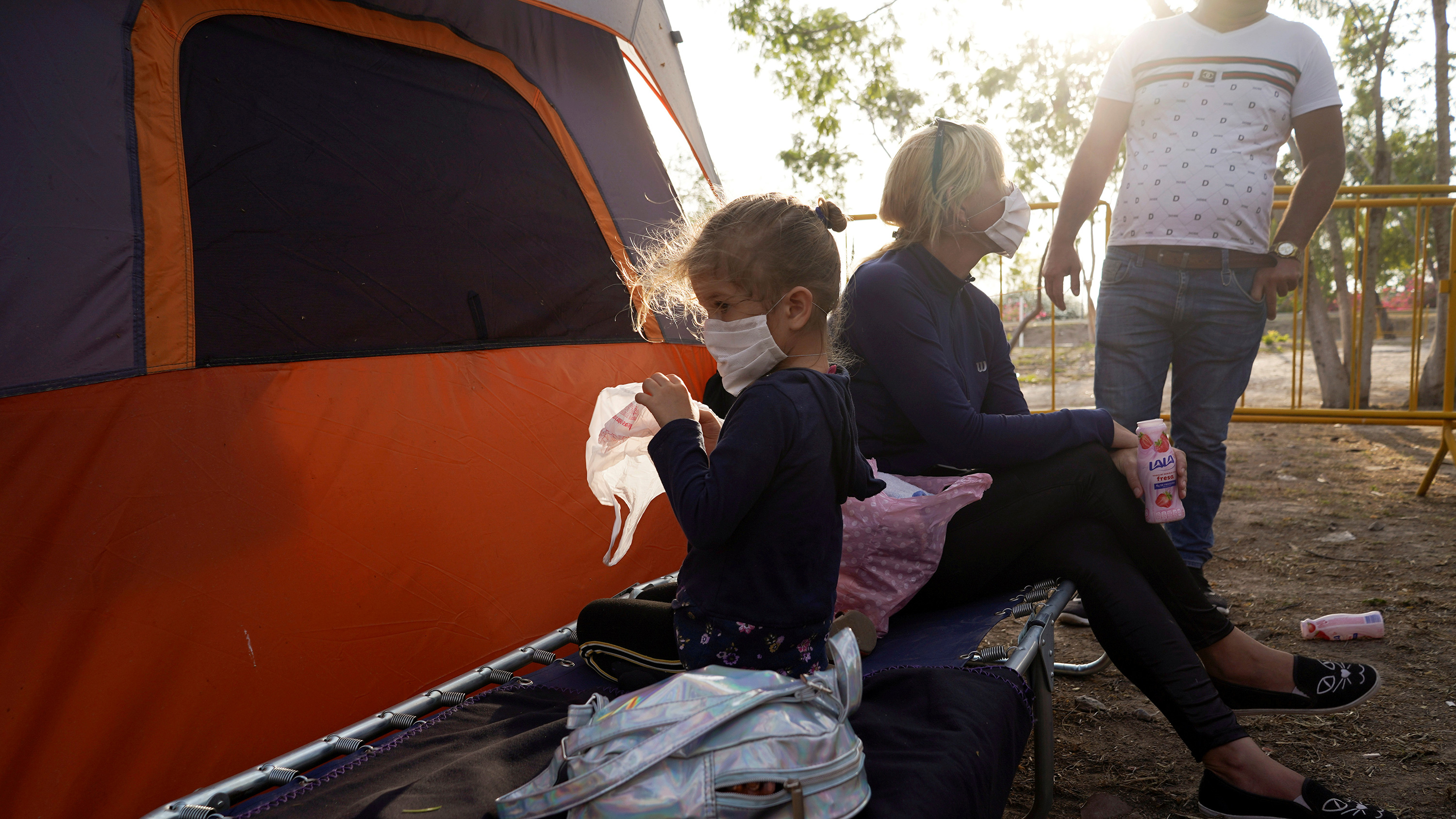 The photo shows the mother and daughter outside a tent in the morning hours with the rising sun brightly illuminating the top of the frame. Mother holds a strawberry drink and talks to a man whose head is out of the frame. Daughter faces the other way and plays with a plastic shopping bag.