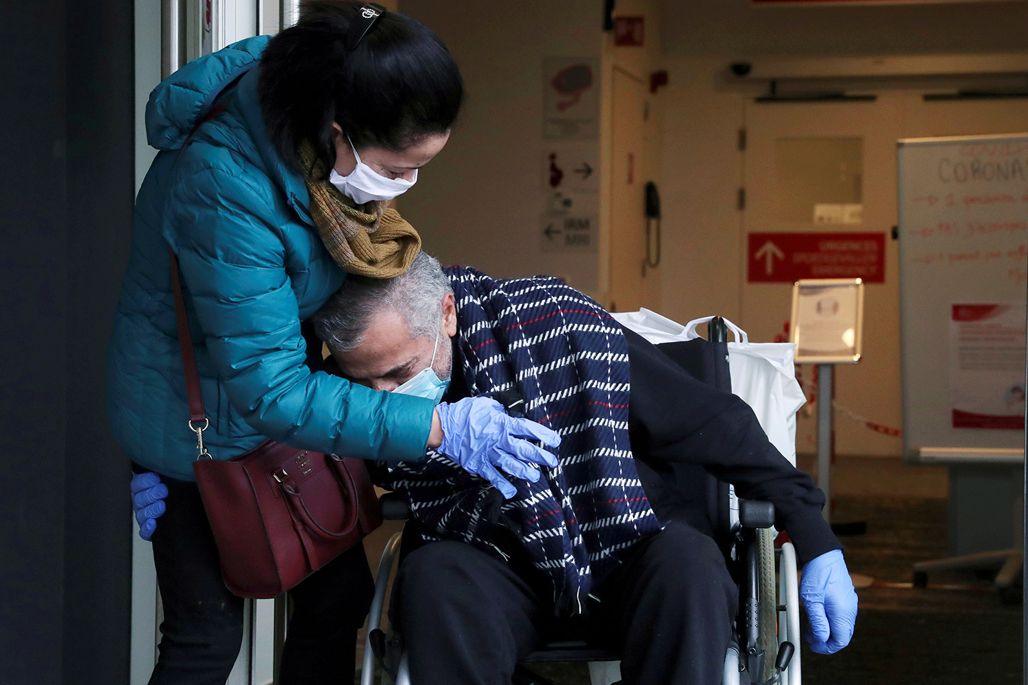 Image shows the doctor in a wheelchair hugging at his wife's torso as she leans into him. They are both wearing masks and gloves.