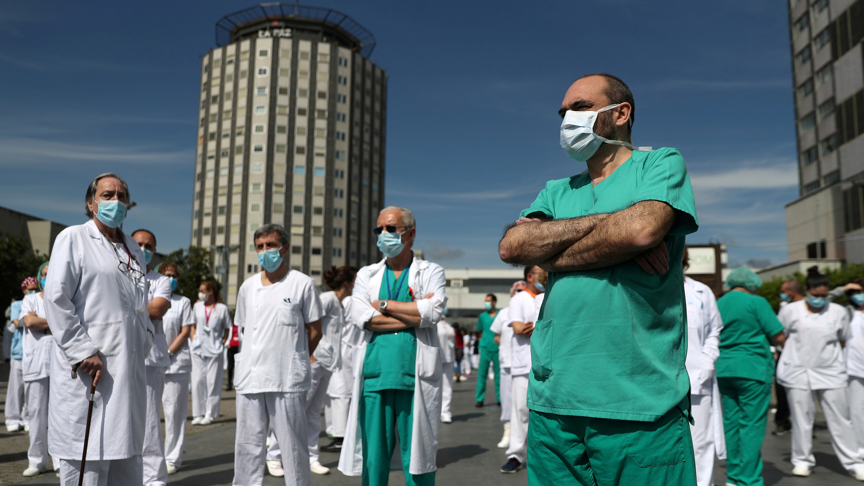 The photo shows a number of medical staff standing around in the bright, bright sunlight talking.