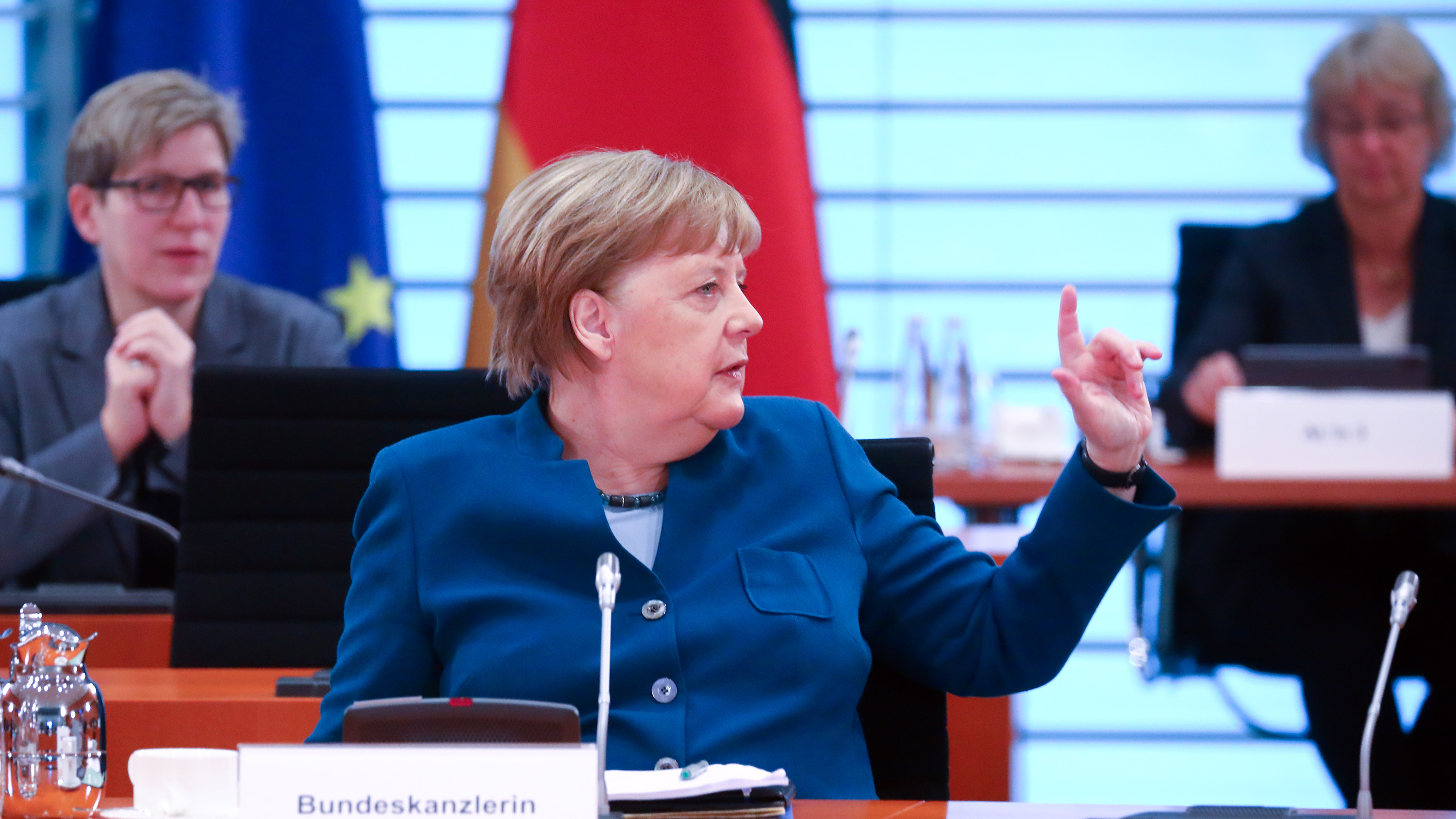 The photo shows the German chancellor at a table turning to her side gesturing to someone off camera.