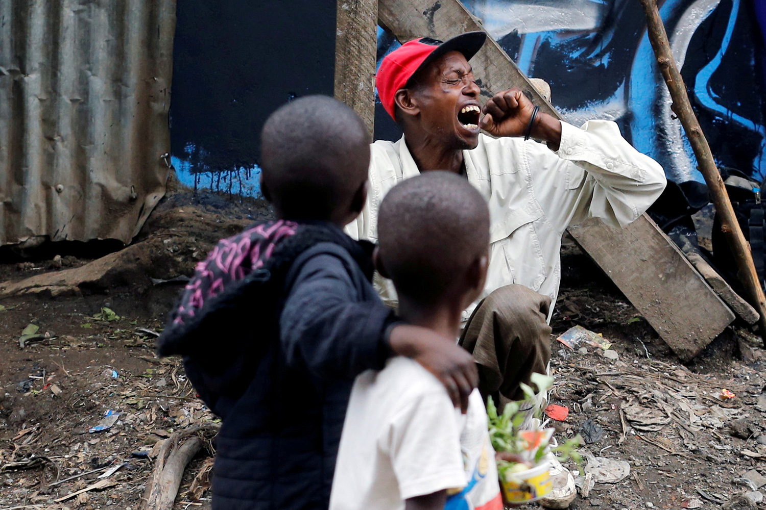 A man coughs as children walk past roadside, during the coronavirus pandemic in Nairobi, Kenya April 19, 2020. This is a powerful image of two children looking at a man who is coughing into his had with his head turned. REUTERS/Thomas Mukoya