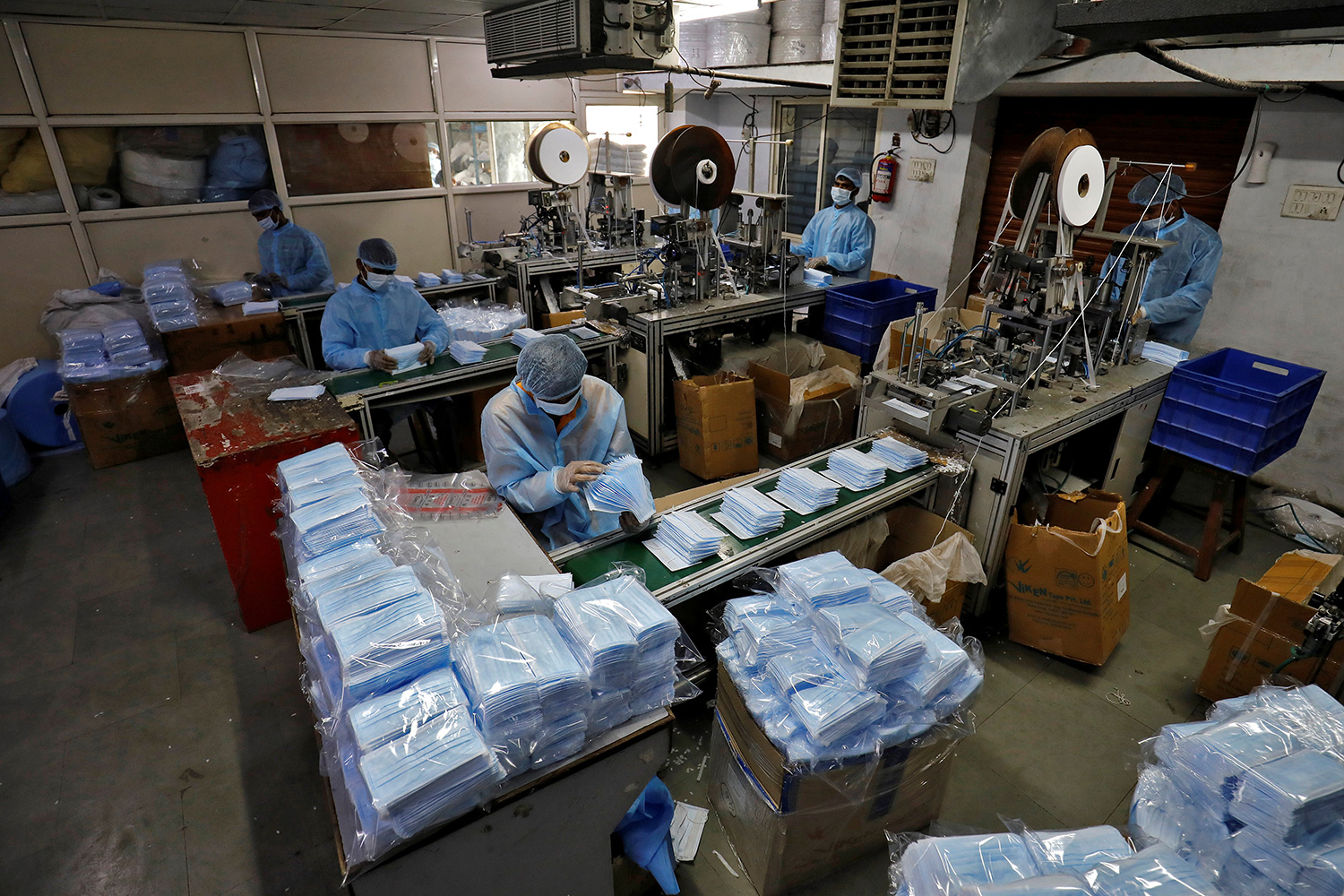 The photo shows a factory interior where several workers are at stations stacked high with blue surgical-style masks.