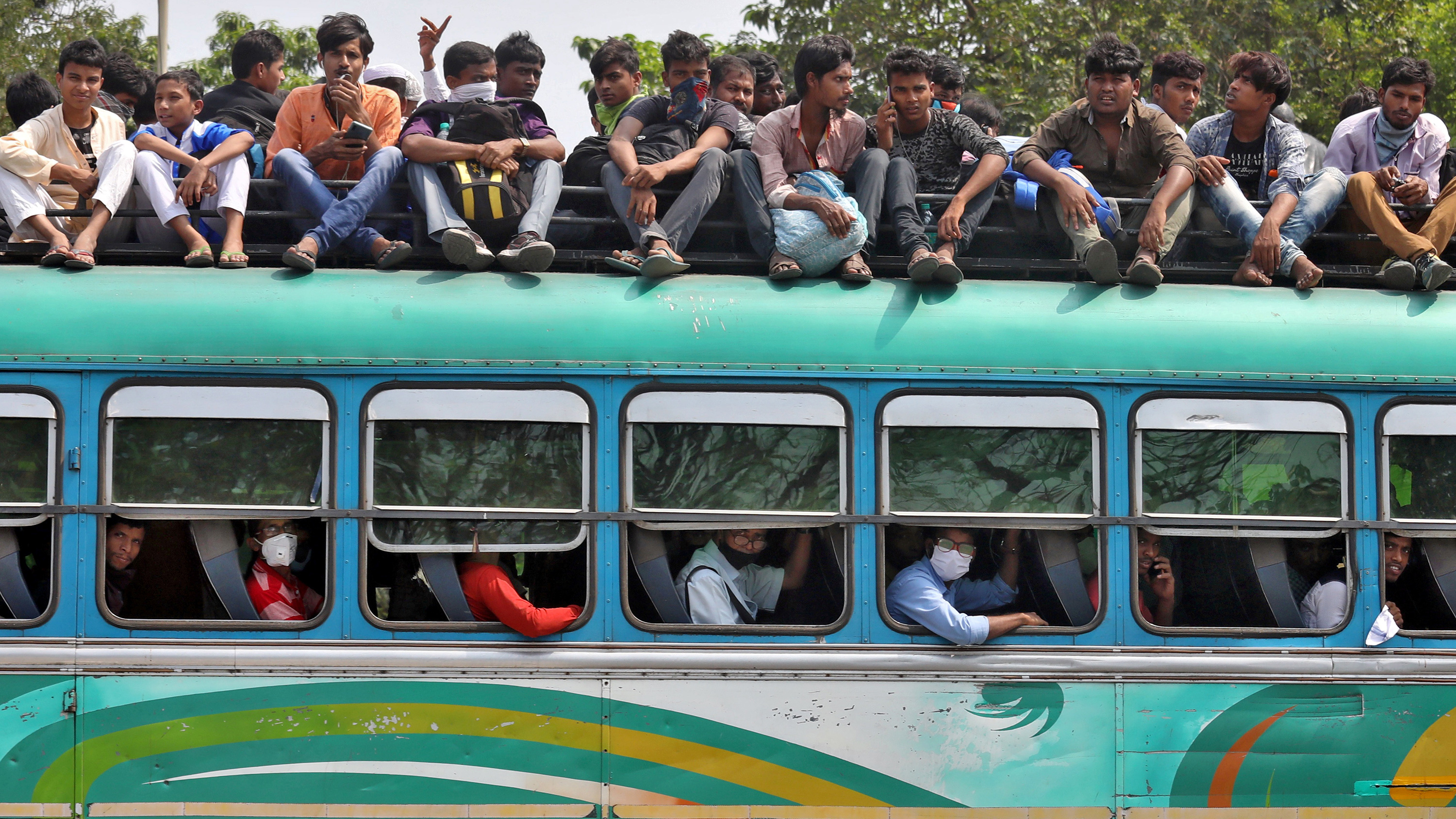 This is a stunning photo of a passenger bus with people sitting on top and in all the aisles inside.