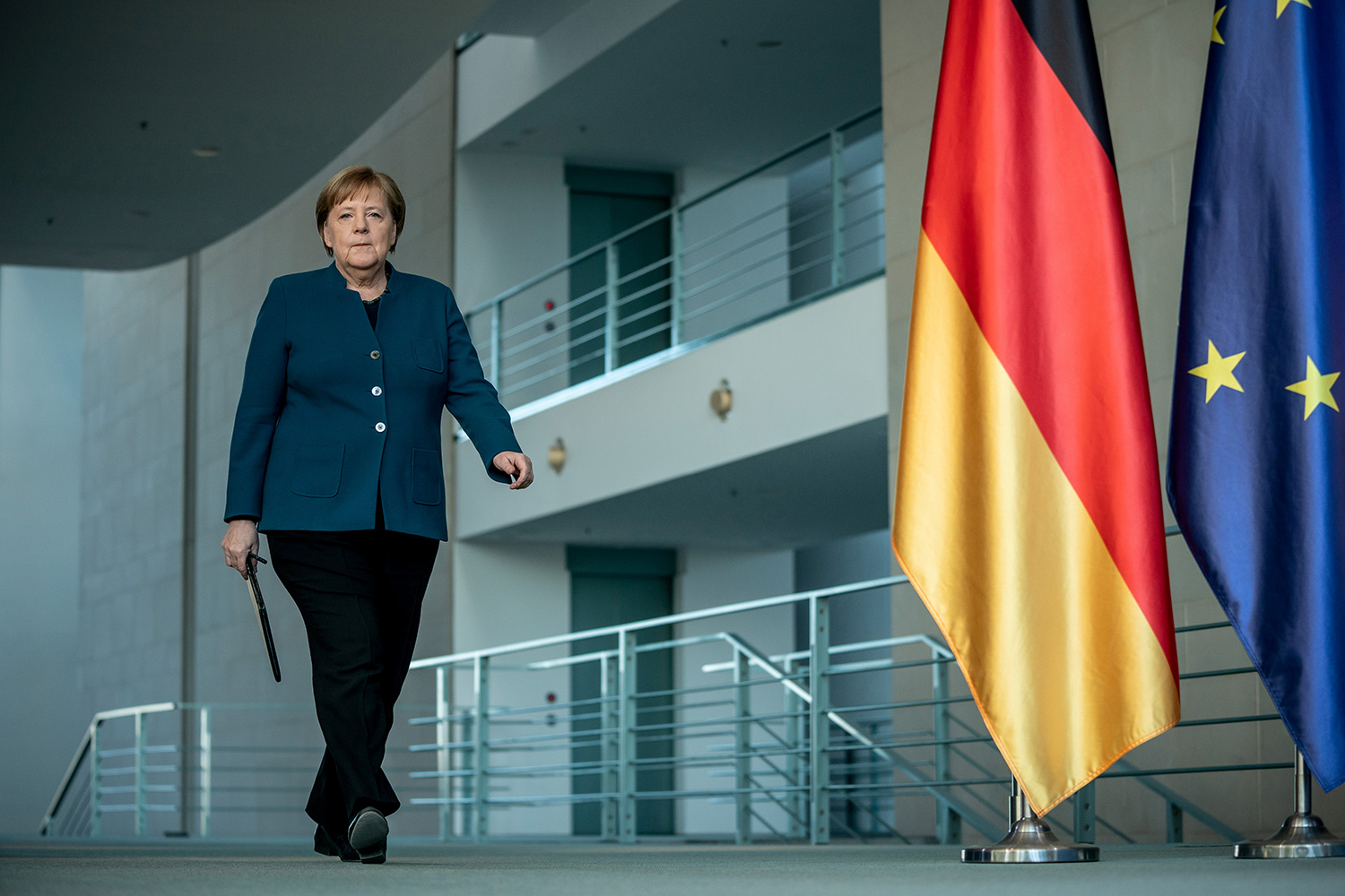 The photo shows the German leader walking through a building interior next to a German flag.