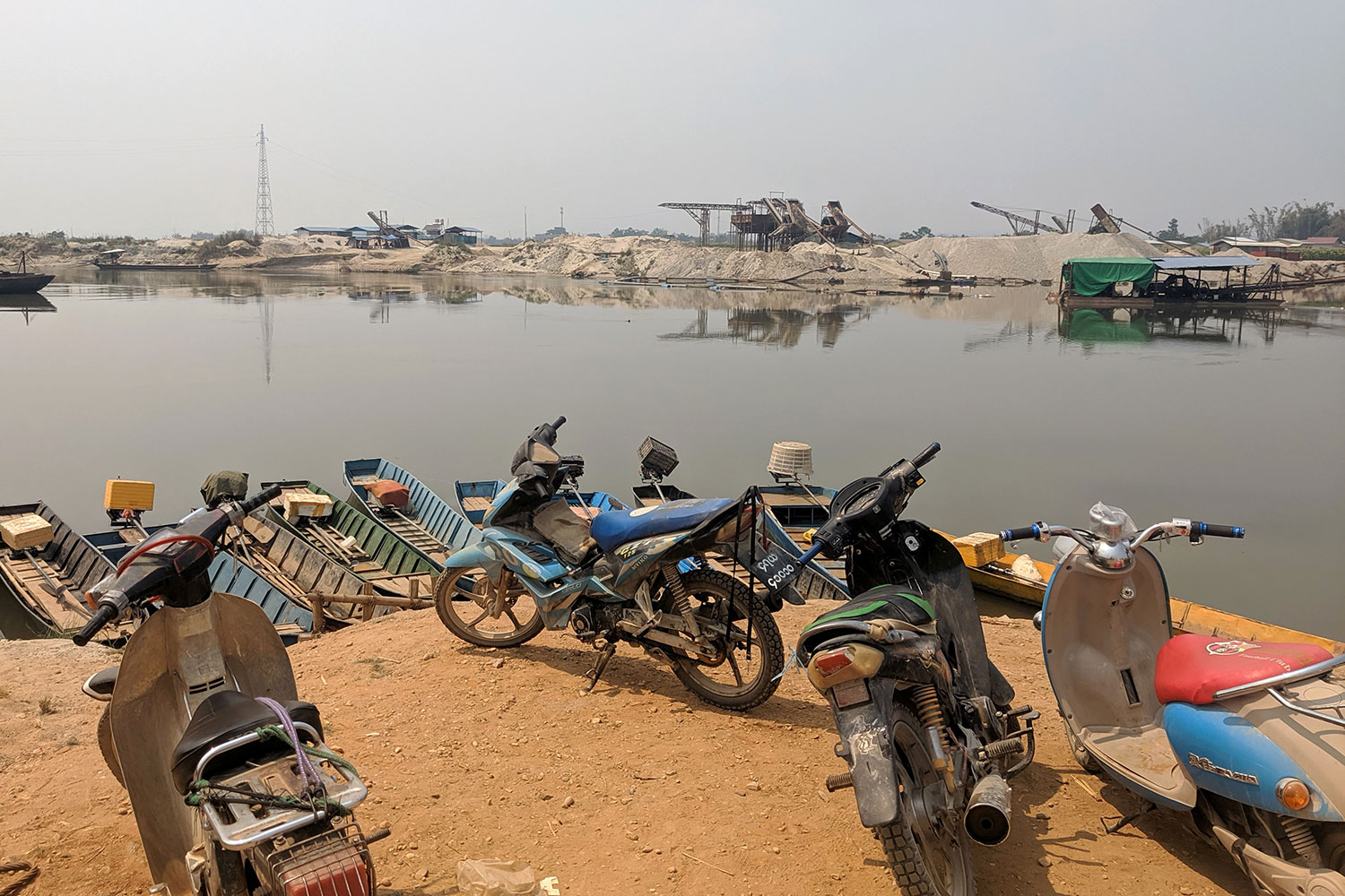 The photo shows an areae looking across a body of water with a number of motorbikes parked in the foreground.