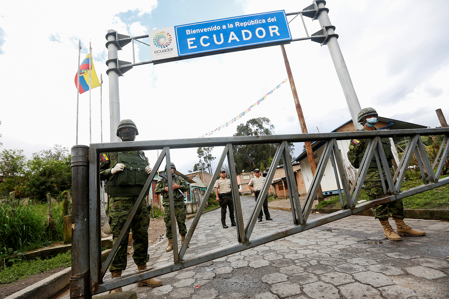 Soldiers on the Ecuadoran side of the border with Colombia, in Tufino, Ecuador, after their government announced the closure of borders to all foreign travelers due to coronavirus on March 15, 2020. The photo shows a border crossing with a large sign reading, Ecuador, and several soldiers in the frame. REUTERS/Daniel Tapia