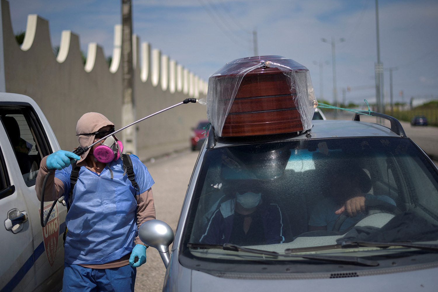 The photo shows a health worker in protective gear spraying a vehicle.