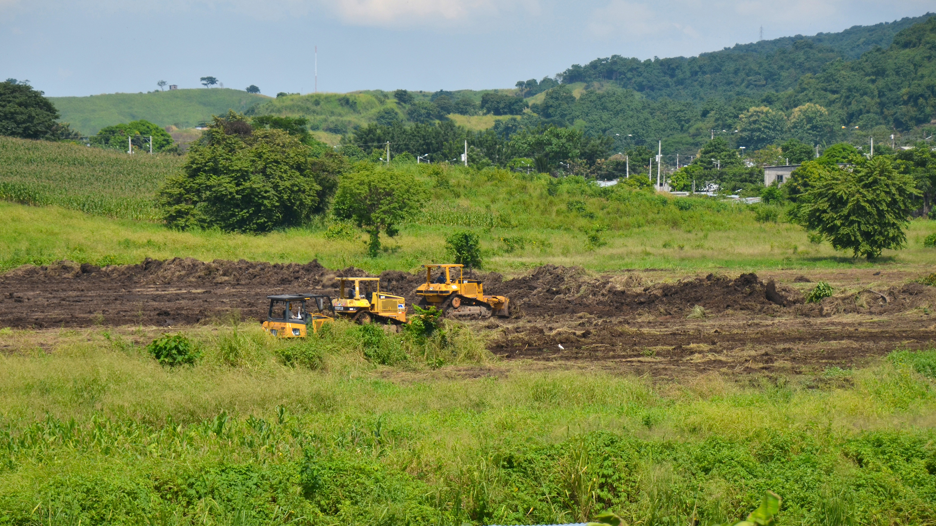 Picture shows a lush green landscape with some heavy machines clearing the ground.