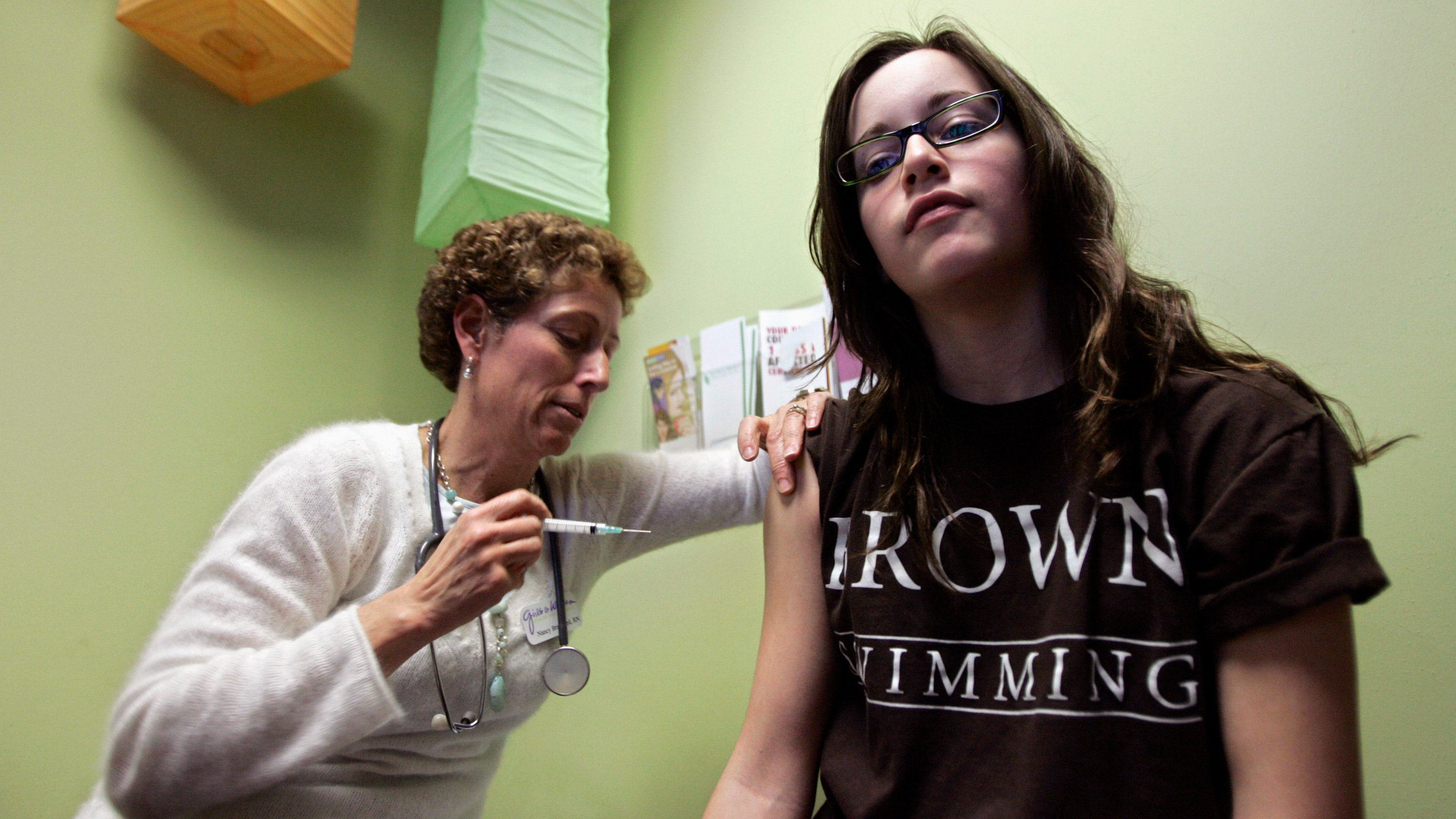 The photo shows a nurse giving a shot to a teemage girl who is looking straight at the camera.