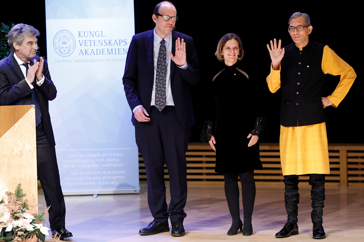 Image shows the three nobel laureates posting for pictures on the stage and waving at an audience, presumably to thundrous applause.