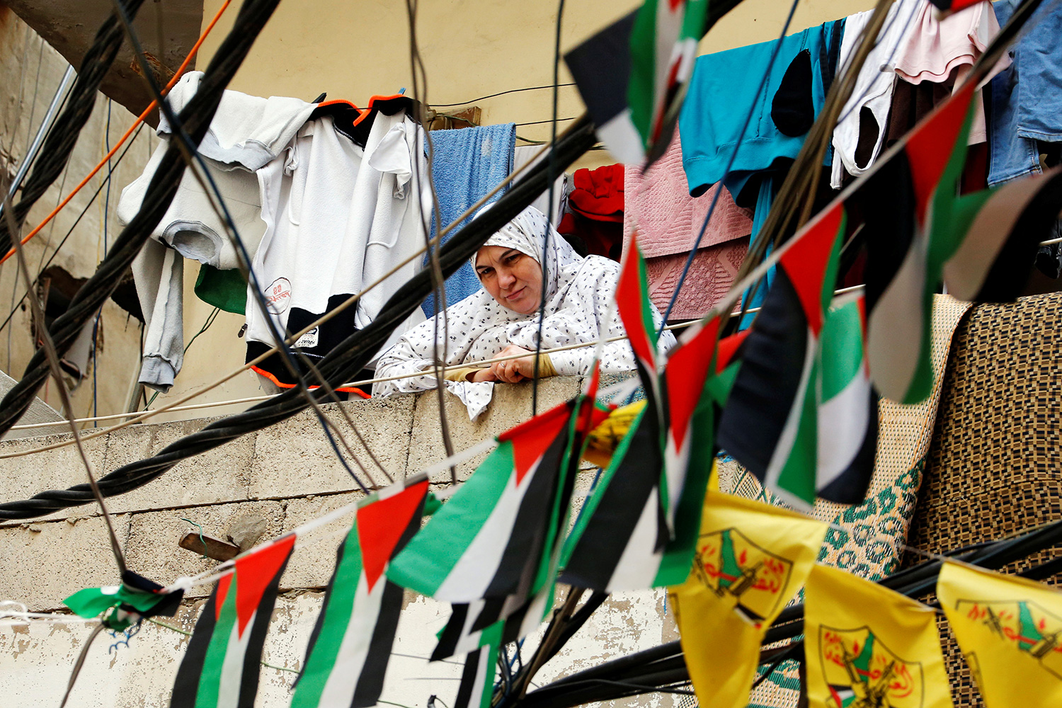 Picture shows the woman looking down at the camera from a balcony above. Clothes strewn on a line behind her and a string of Palestinian flags hung between her and the camera visually mix to make the scene very busy with billowing cloth.