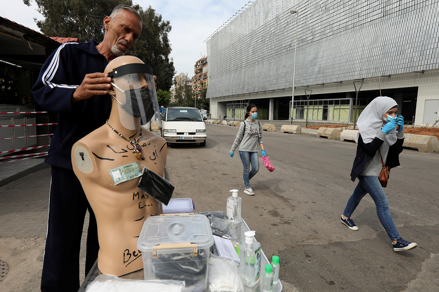 The photo shows the man fitting a clear plastic mask on a manikin next to a makeshift huckster table on a busy street with people walking by.