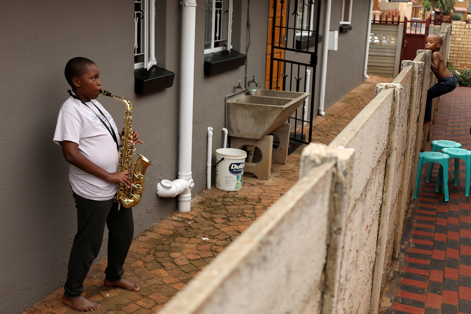 The photo shows a teenage boy playing a huge sax while another, younger boy scambles up over a fence.