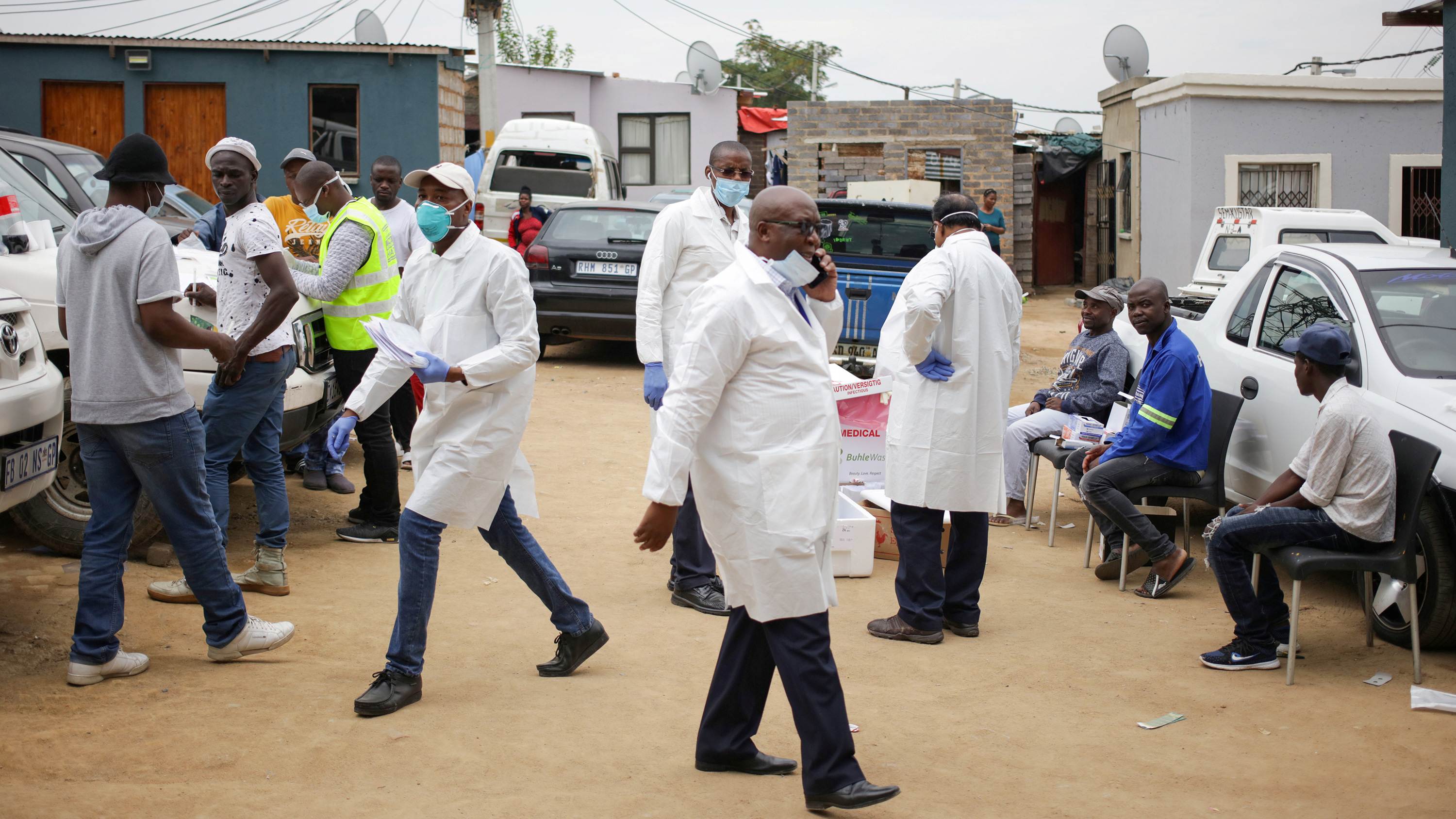 The photo shows about a half dozen health workers wearing white lab coats and a number of civilians waiting to be tested.
