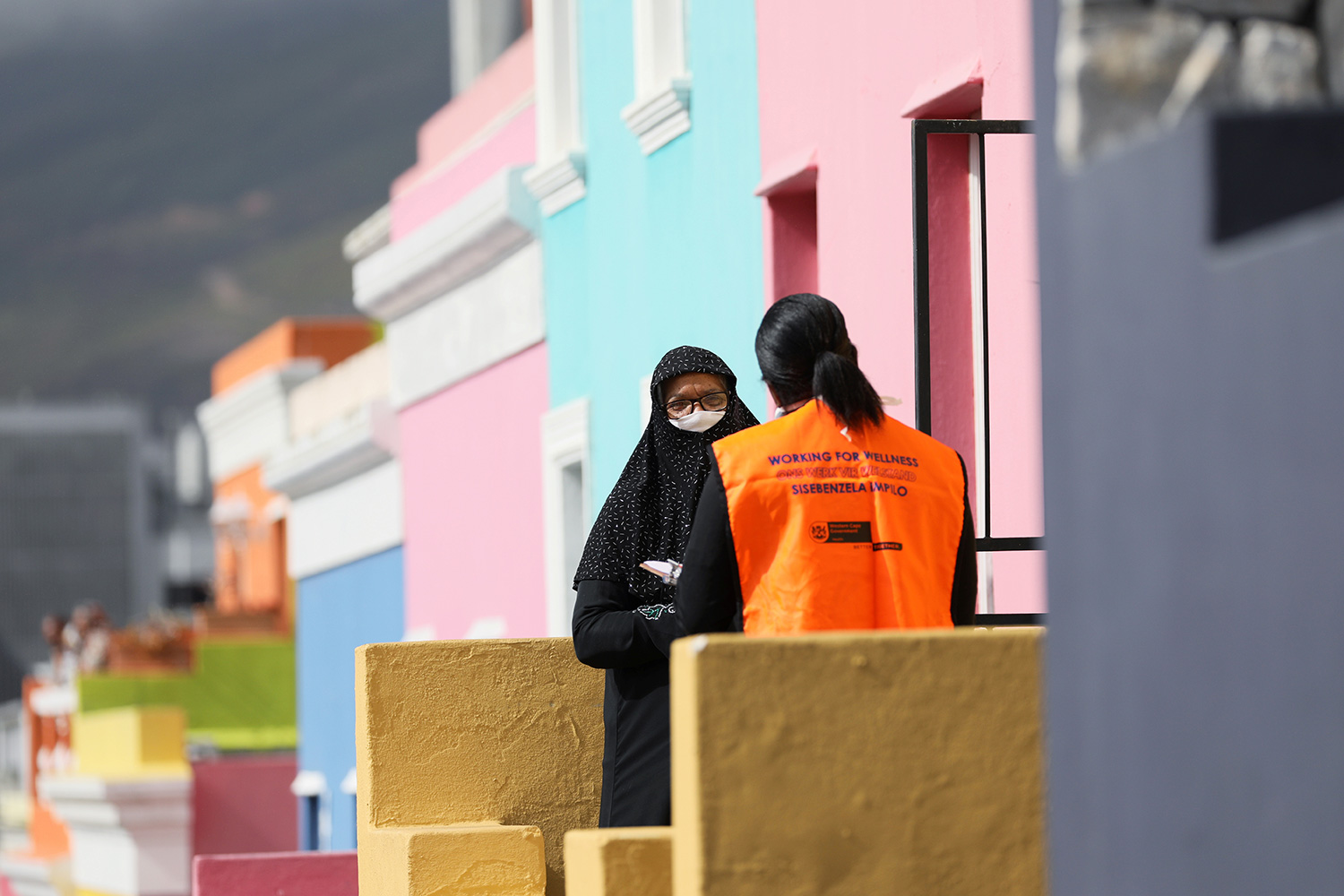 The photo shows the health care worker from behind speaking to a women wearing a head scarf and mask and facing the camera. They are standing on the front steps of a series of houses that are brightly colored green and orange and pink and purple pastels.