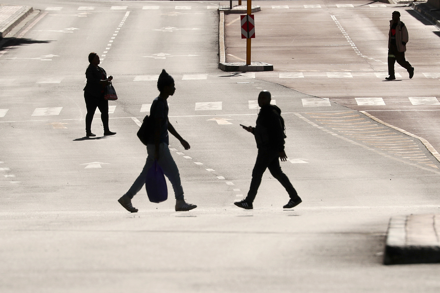 People cross normally busy—now largely empty—Adderley Street in central Cape Town, South Africa, on April 14, 2020, during the 21-day nationwide lockdown aimed at limiting the spread of coronavirus. This is a stunning photo showing a broad main thoroughfare that is completely bereft of cars. Four people are seen crossing the wide street, each silhouetted against the early or late sun reflecting off the asphalt pavement. REUTERS/Mike Hutchings
