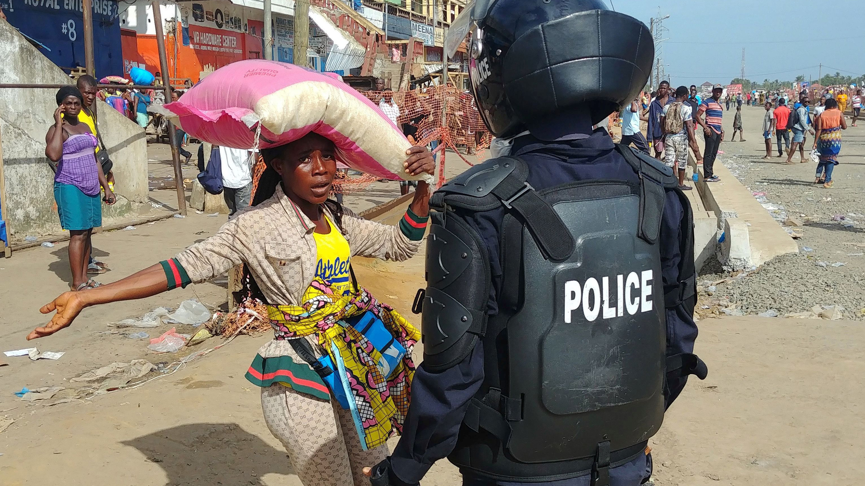 Picture shows a woman with a large sack hoisted above her shoulders confronted by a uniformed police officer.