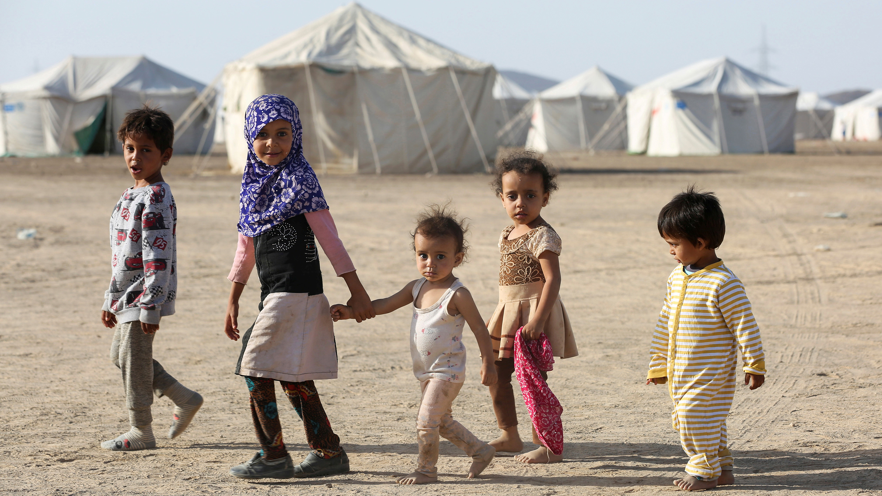 Picture shows a line of five children walking together in front of a camp filled with white tents and looking at the camera. All are very young, two who appear under eight years old, and three who appear under five.