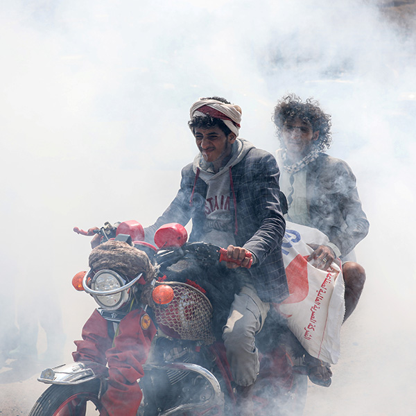 People ride a motorbike amidst smoke from fumigation during a fumigation campaign while the spread of the coronavirus disease (COVID-19) continues, on the outskirts of Sanaa, Yemen, on April 13, 2020. This is a powerful photo showing two men on one motorbike driving through a thick cloud of disinfectant mist. REUTERS/Khaled Abdullah