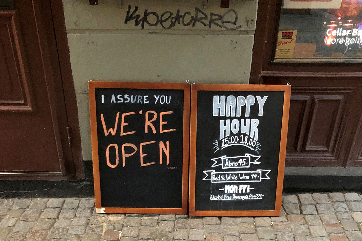 "In a country that didn't lockdown during the coronavirus pandemic, a sign assures people that the bar is open during the COVID-19 outbreak—outside a pub in Stockholm, Sweden, on March 26, 2020. Picture Shows two side-by-side chalk placards in front of a restaurant advertising a happy hour inside. One of the signs reads, ""I assure you WE'RE OPEN."" REUTERS/Colm Fulton"