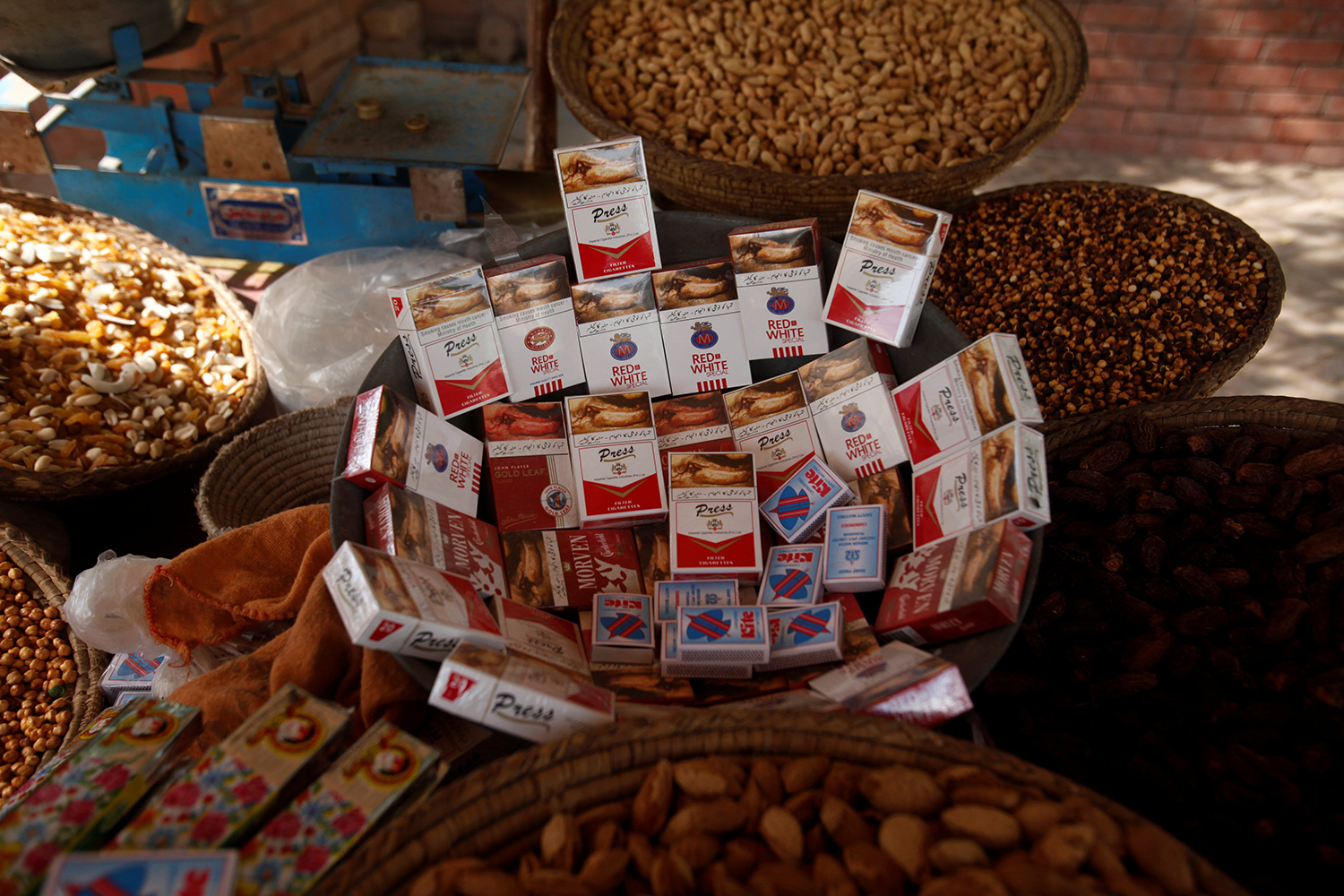The photo shows a street stand with piles of nuts and mounds of smokes.