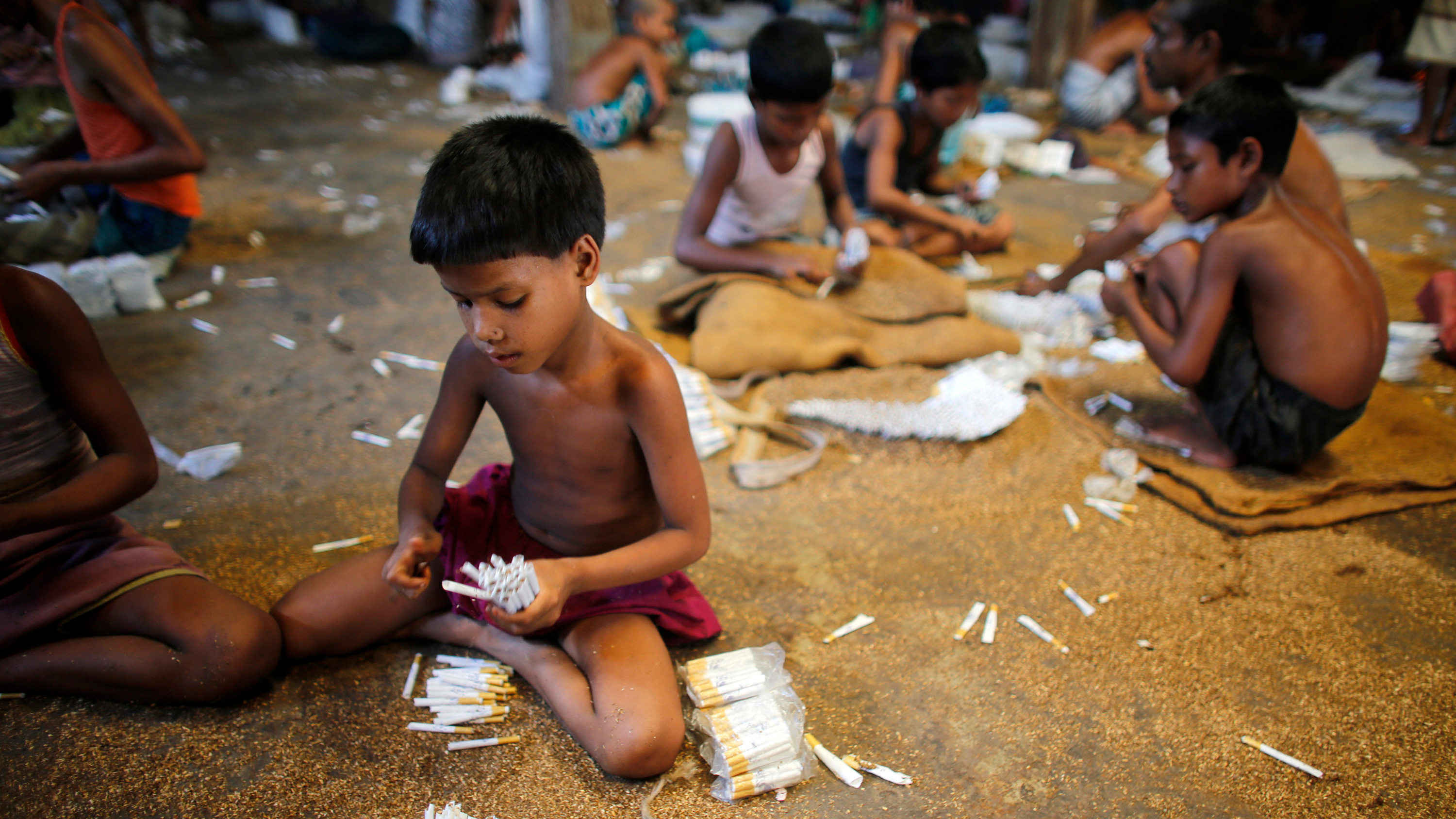 Picture shows several small children sitting around sorting piles of cigarettes.