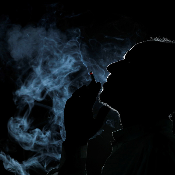 A man is seen in silhouette as he smokes a cigarette at his shop in Peshawar, Pakistan May 28, 2019. The image shows a dark silhouette of a man in profile smoking and filling the air around him with smoke. REUTERS/Fayaz Aziz