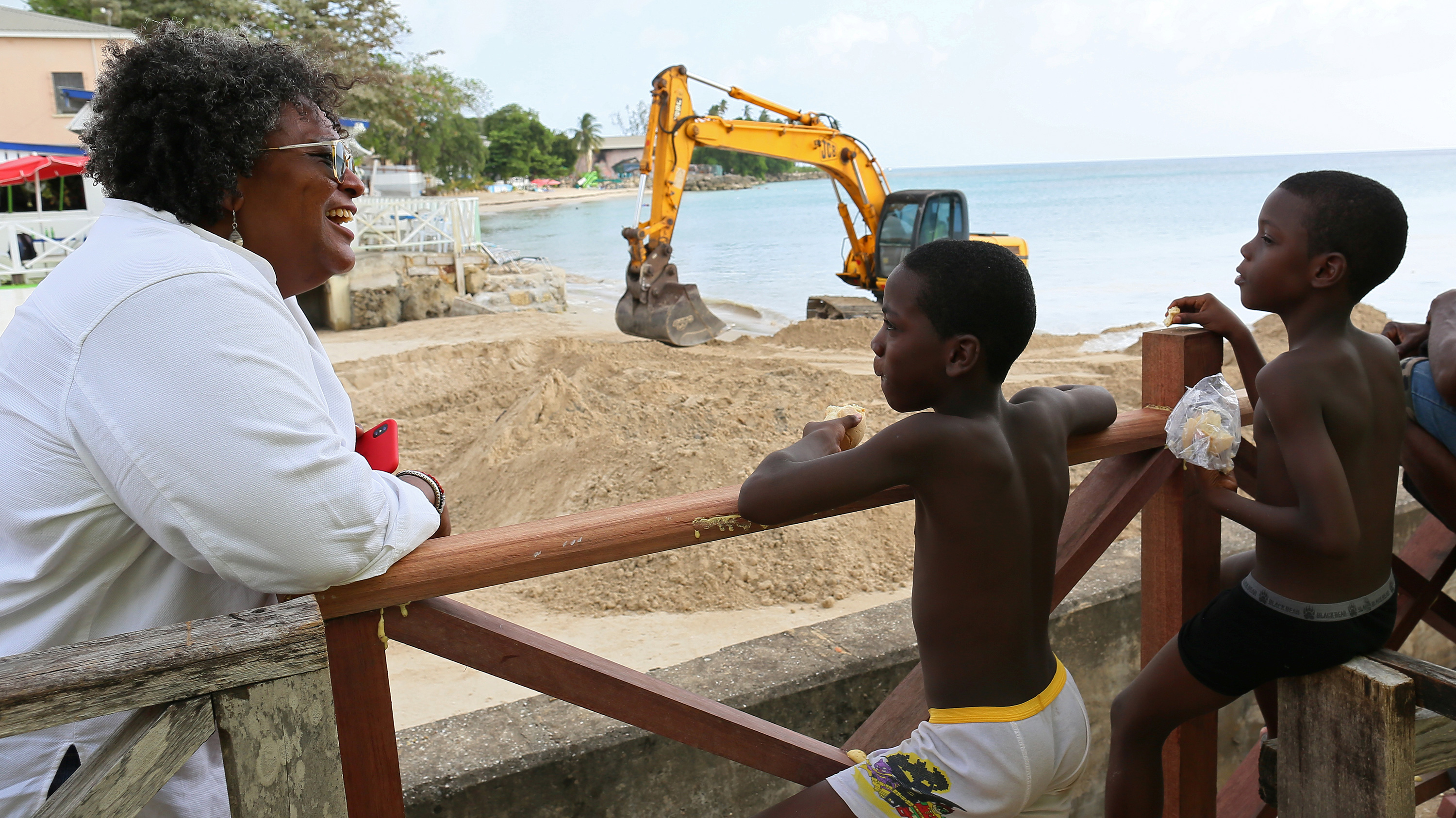 The photo shows the prime minister at the beach leaning on a rail talking to several young children. Construction machinery can be seen in the background.