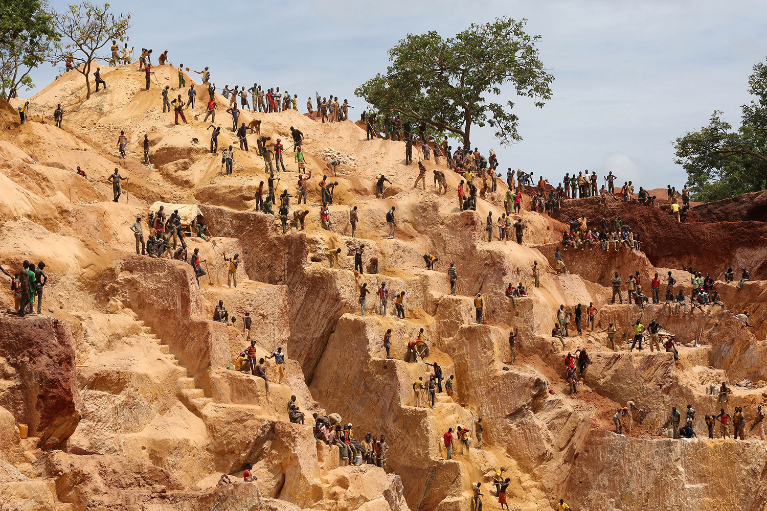 Picture shows the steppes of a small mountain-sized mine cut into the red earth with tiny figures of people everywhere on the different levels.