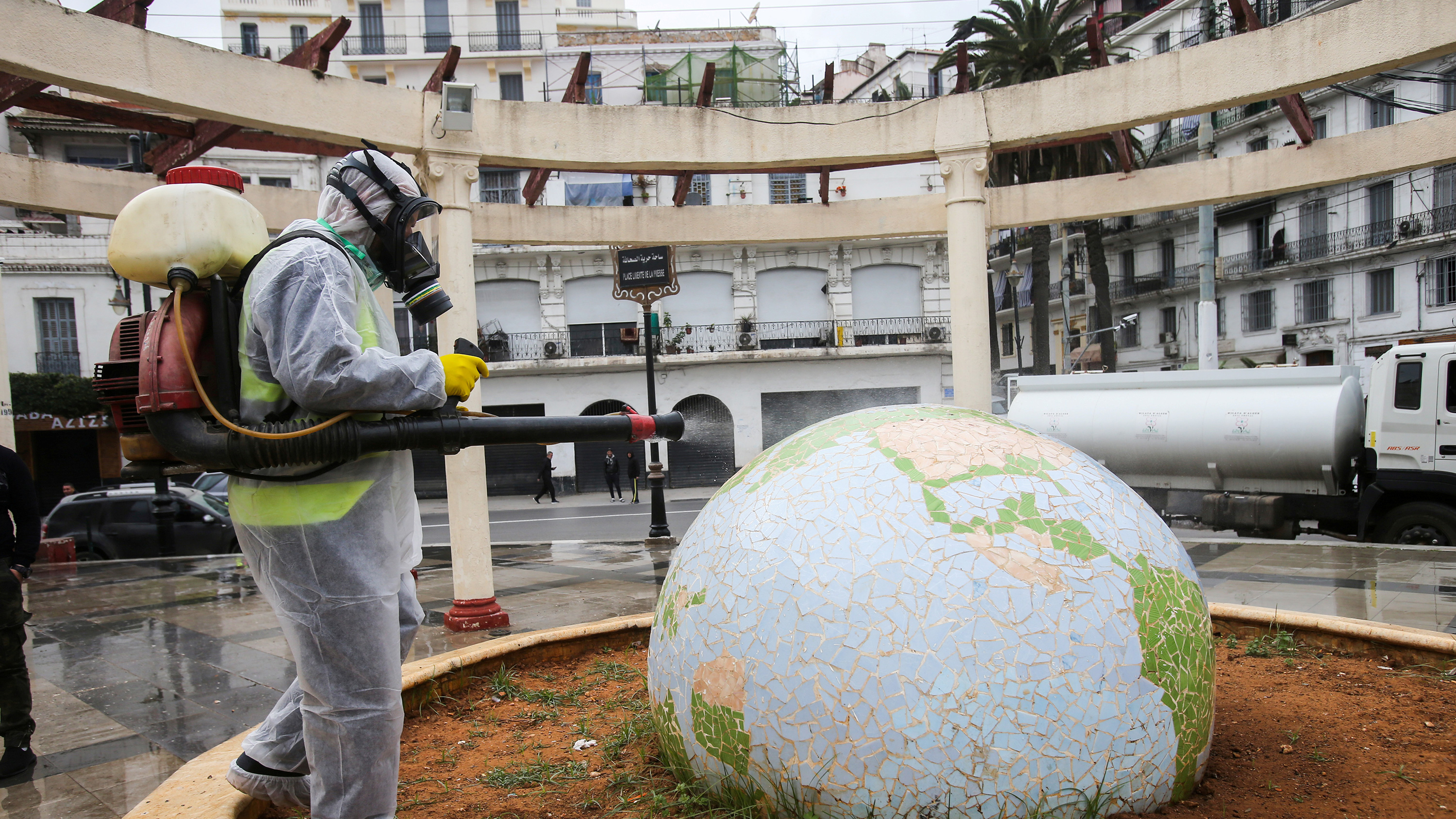 This is a bizarre photo showing the worker in a protective space suit spraying a large, fancy globe sculpture in the center of an open-air atrium.