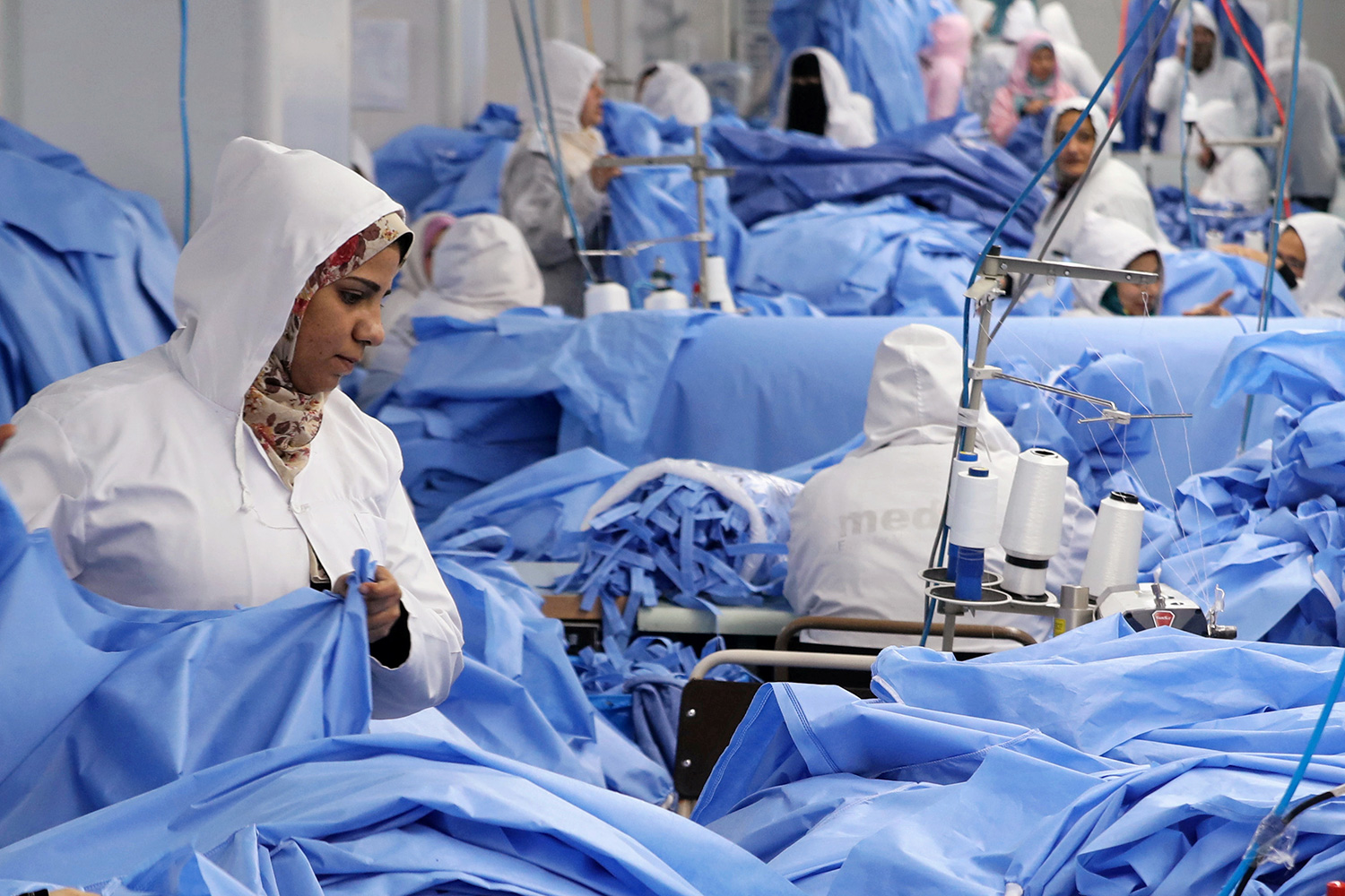 Picture shows blue—lots of blue. The workers are in white protective clothing in the factory assembly area, working among stacks of blue fabric.