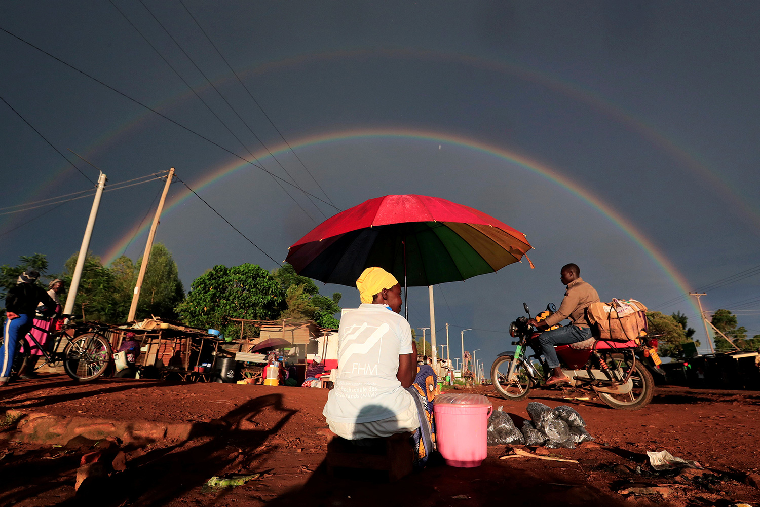 A double rainbow is seen above a woman holding an umbrella and selling snacks along the road in Siaya County, Kenya, on May 3, 2020, in the midst of the coronavirus pandemic. This is a spectacular photo that shows a woman under a bright red umbrella from behind as she is sitting on the side of the road greeting passer-bys with a full-double rainbow highlighting a storm-darkened sky in the distance. REUTERS/Thomas Mukoya