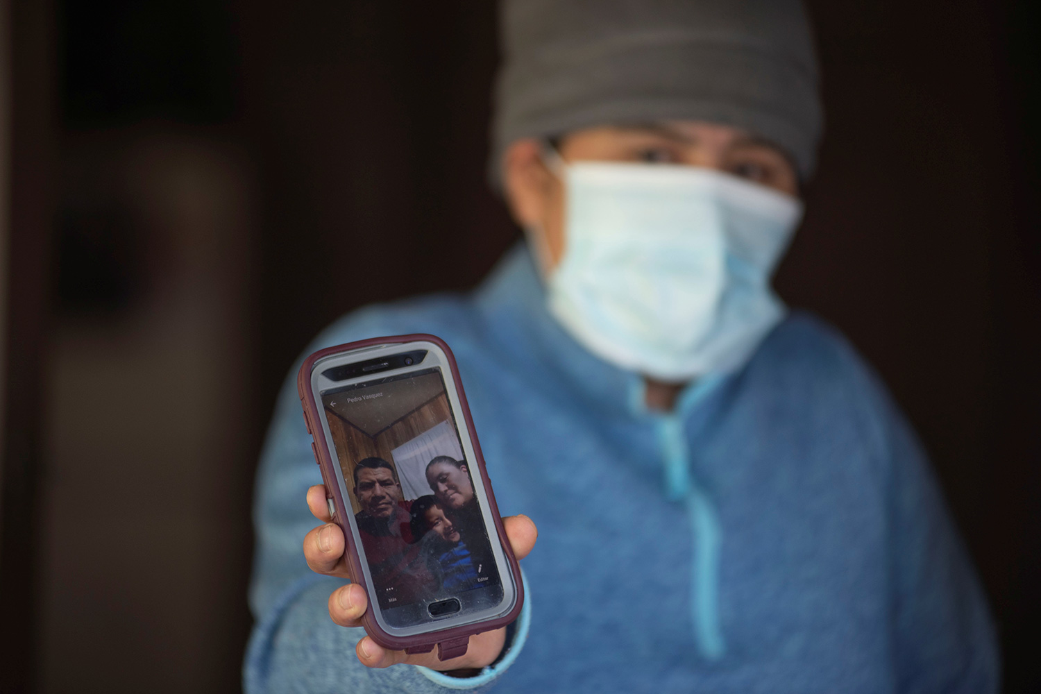 Picture shows Zoila holding a cell phone for the camera and wearing a mask. The photo on the phone shows the small family in happier times.