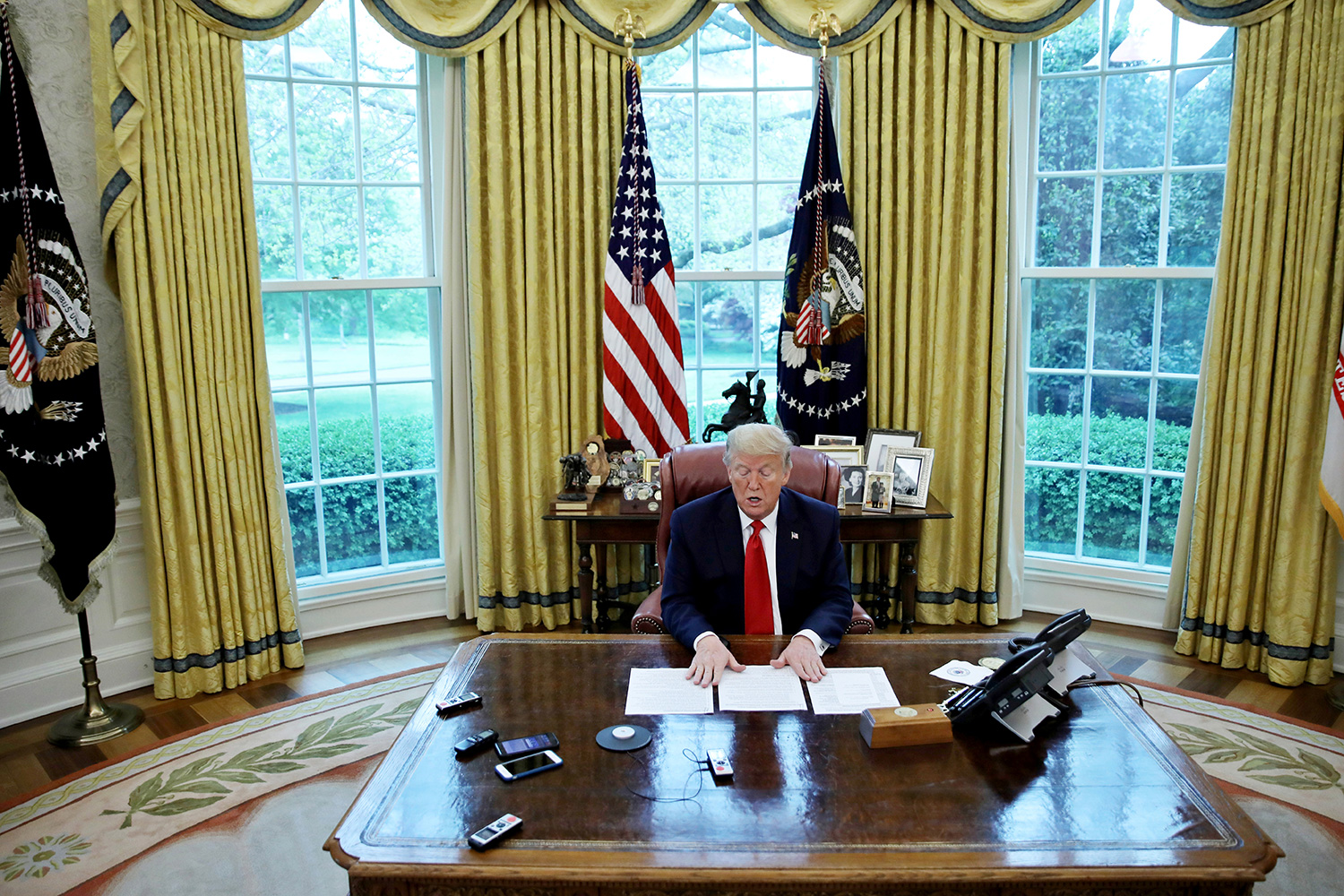 U.S. President Donald Trump looks at his briefing papers as he answers questions during an interview with Reuters about China, the coronavirus pandemic and other subjects on April 29, 2020. The photo shows the president at his desk in the Oval Office. REUTERS/Carlos Barria