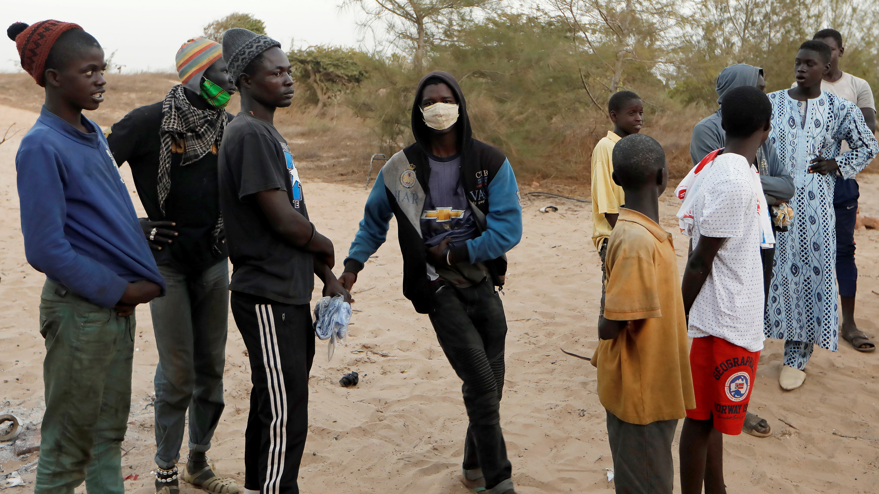 Picture shows a number of teenage boys standing around. One of them is wearing a mask.