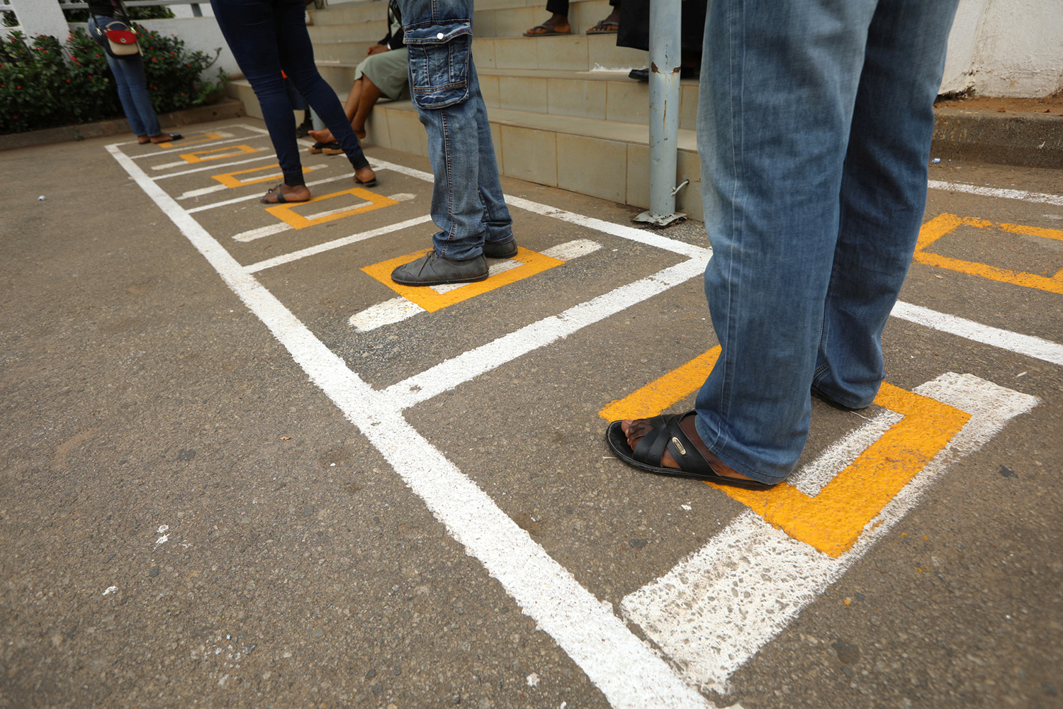 Photo shows the legs of several people standing in social distancing squares painted on a blacktop as they wait in line.