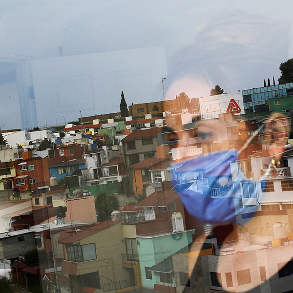 Monica Samudio, 46, whose husband Jorge Garcia, 51, died from coronavirus looks out of her window in Mexico City on April 29, 2020. Samudio faced discrimination when she contracted the disease. Picture shows the woman looking out her window and partially reflected in the glass. REUTERS/Edgard Garrido