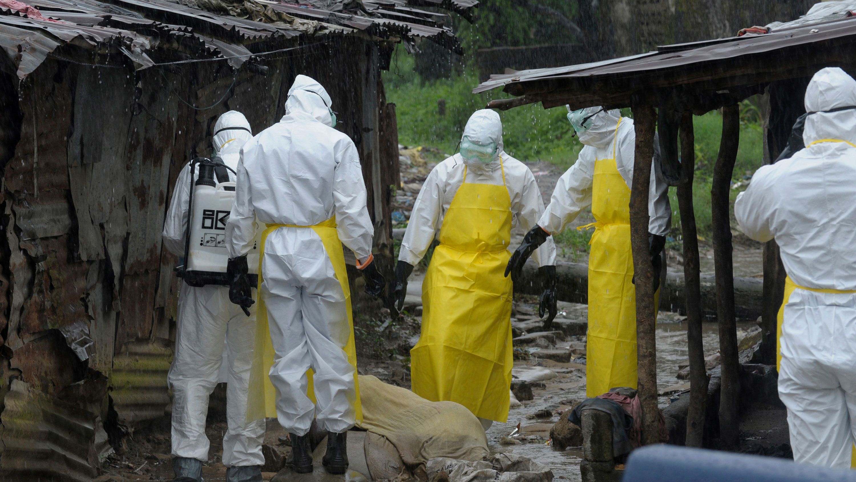 The photo shows half a dozen workers in full body protective suits standing in large mud puddles in the driving rain beside a body draped by a thin muslin cloth in between some ramshackle shacks. Some are pointing, and they appear to be discussing how to pick up the deceased victim.