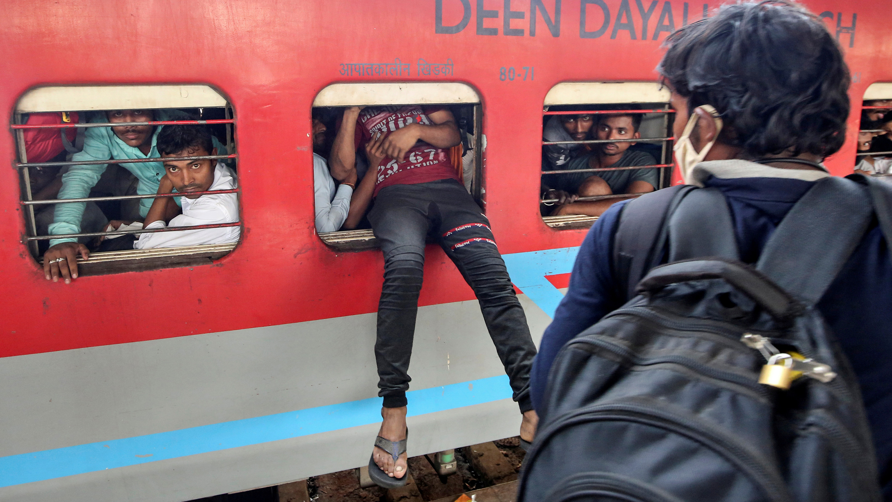 This is a striking photo of someone trying to scramble through the open window of a bright red passenger car on a train. Their legs from the waist down dangle precariously out the window.