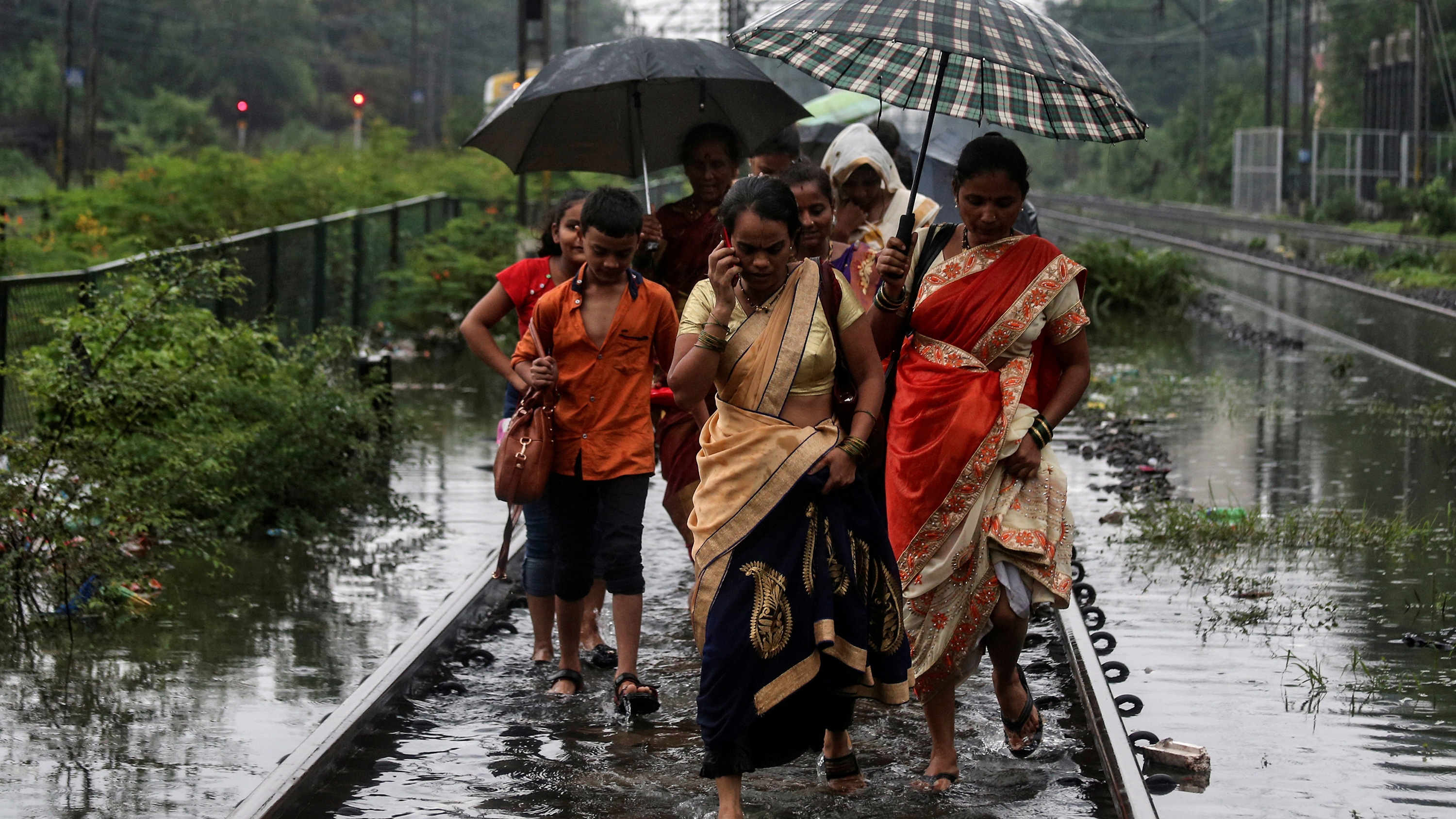 The image shows several people walking ankle-deep in water along railroad tracks as they hold several umbrellas over their heads in the rain.