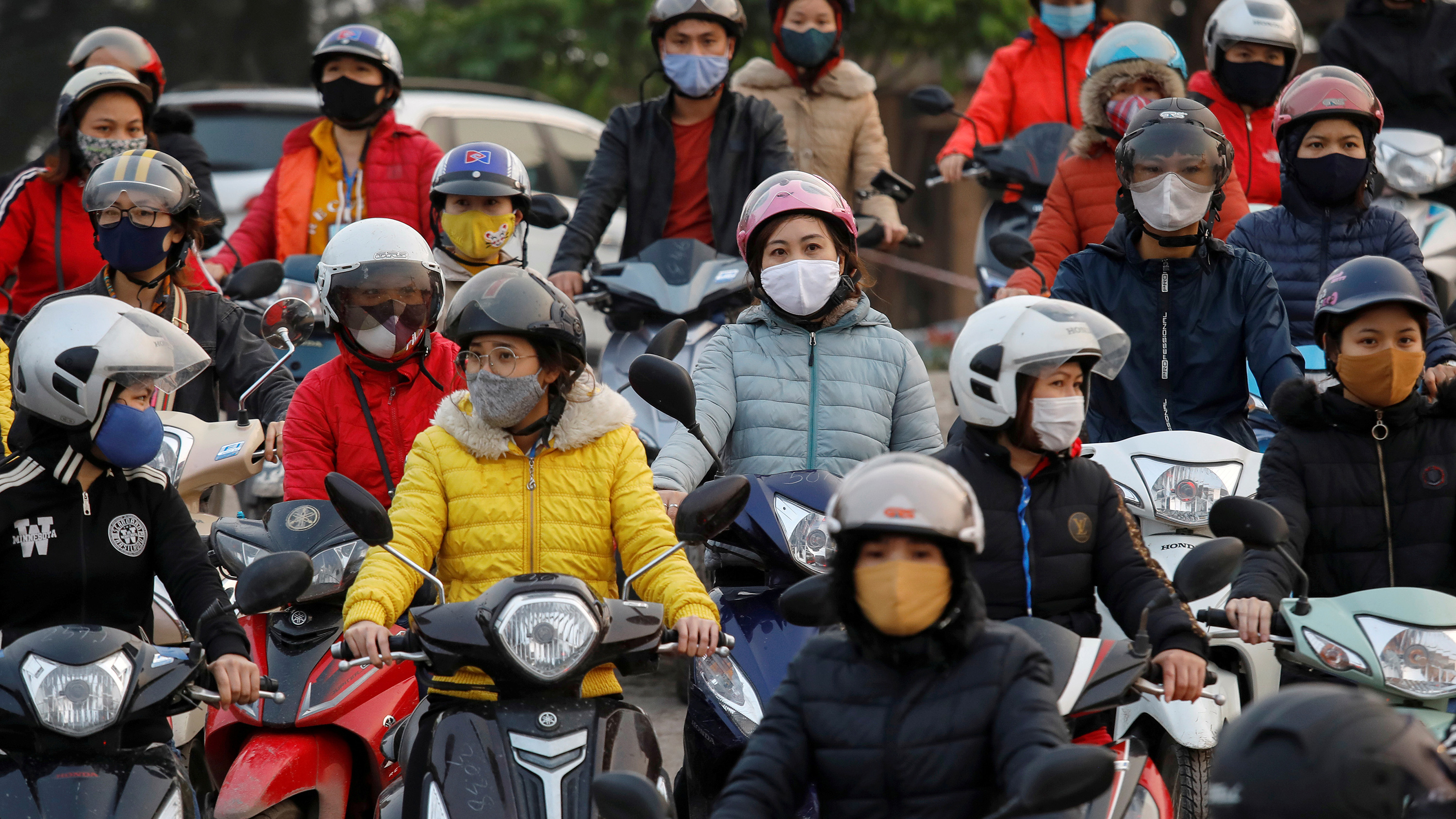 Laborers wearing protective masks gather while they wait for a ferry on the way home after work during the coronavirus outbreak in Hai Duong province, Vietnam, on April 7, 2020. The image shows a number of people on motorcycles wearing masks.