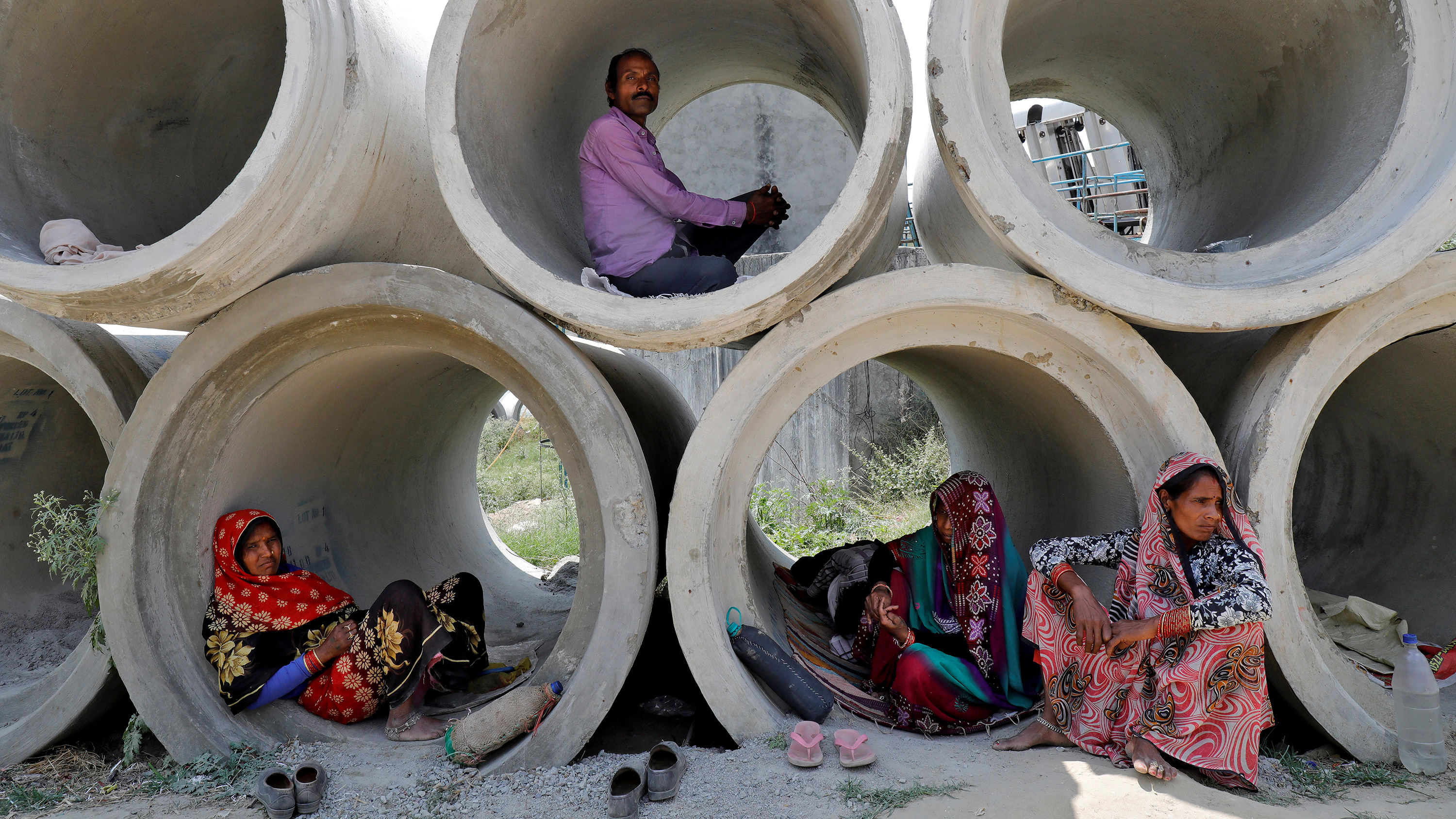 This is a powerful image of people inside stacked cement pipes of large enough diameter for them to camp out in.