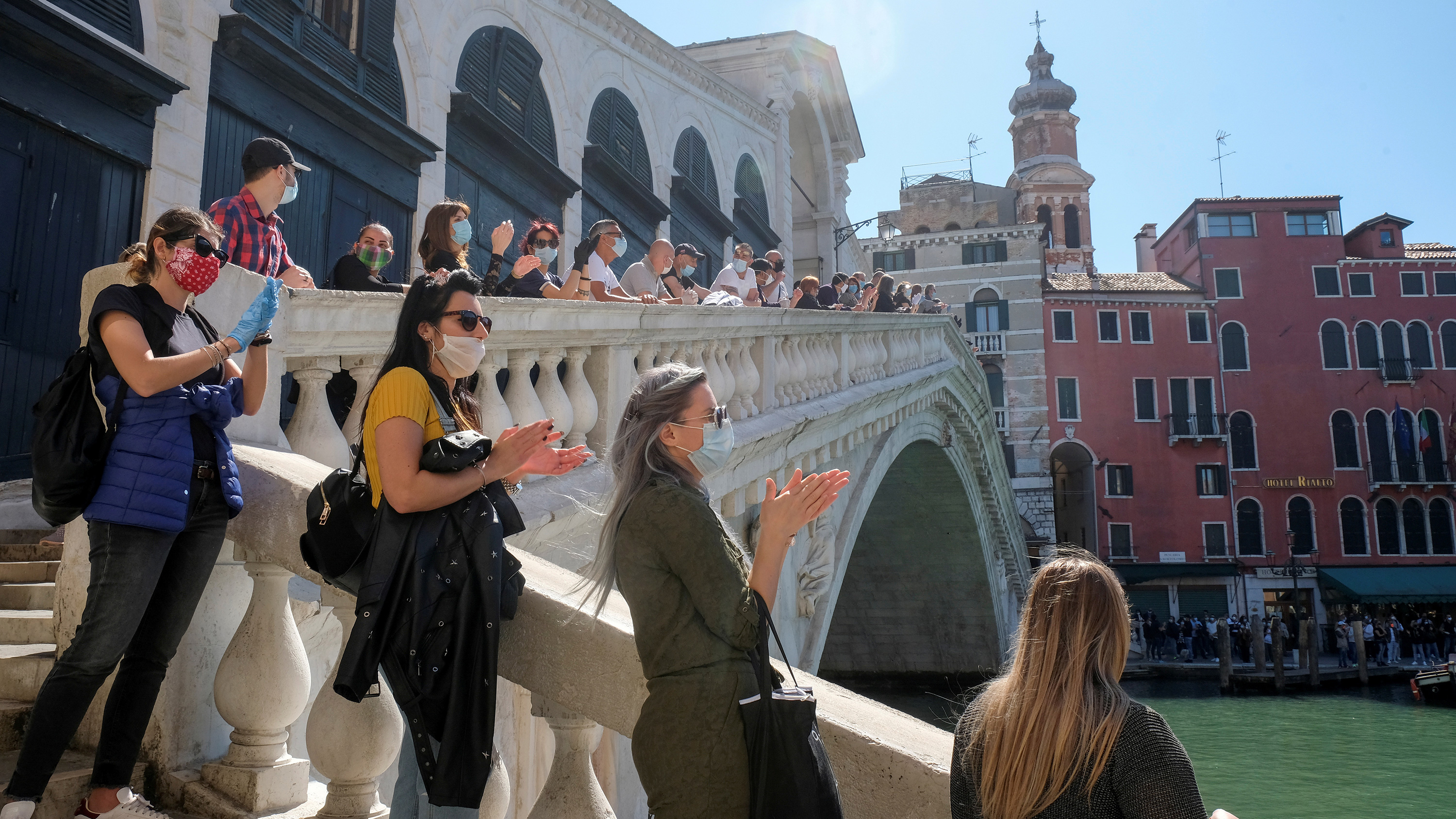 The photo shows a line of people social distancing standing on a picturesque bridge on a beautiful sunny day.